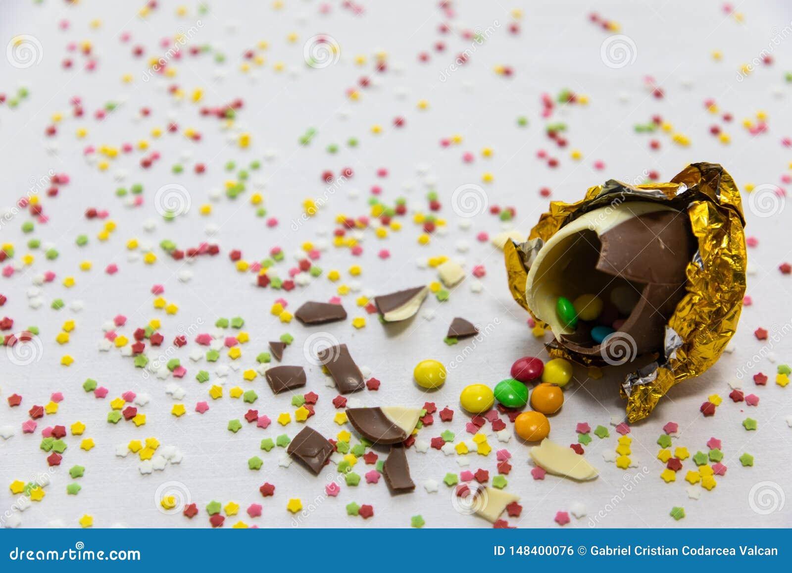 Ovos da p?scoa dourados quebrados do chocolate com chocolates coloridos para dentro no fundo branco com confetes borrados colorid