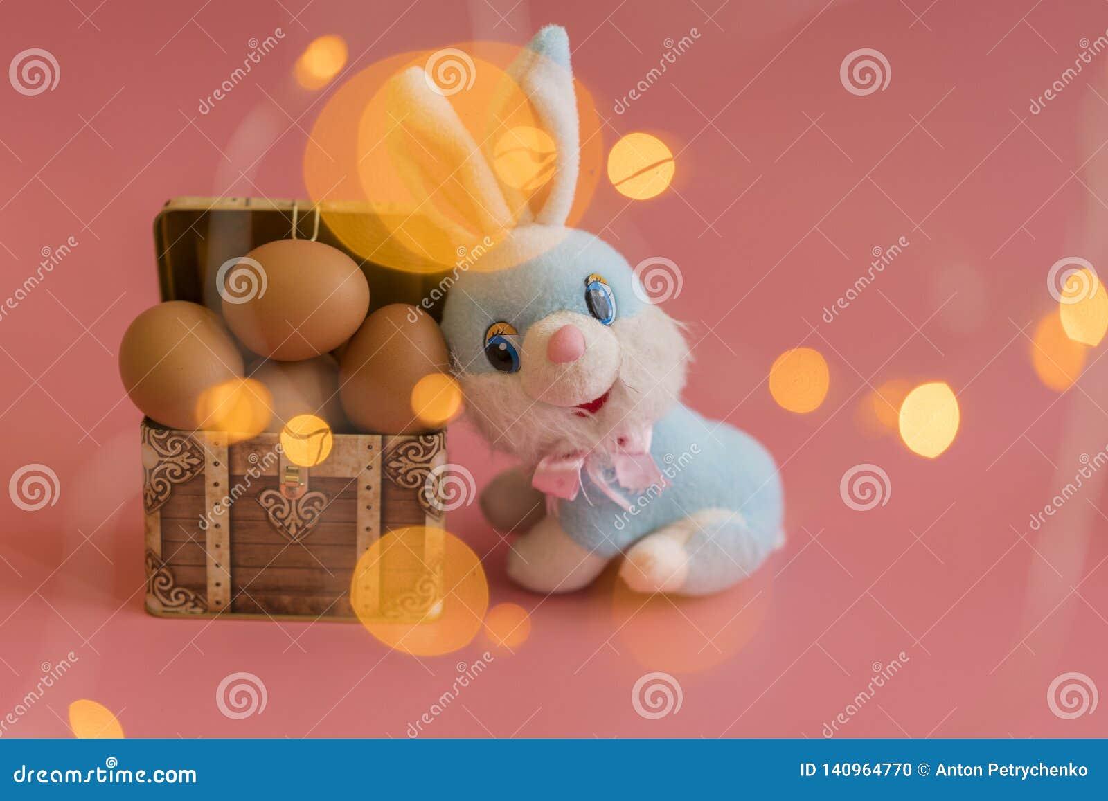 Ovos em uma caixa e em um coelhinho da Páscoa Conceito da Páscoa no fundo cor-de-rosa Bokeh