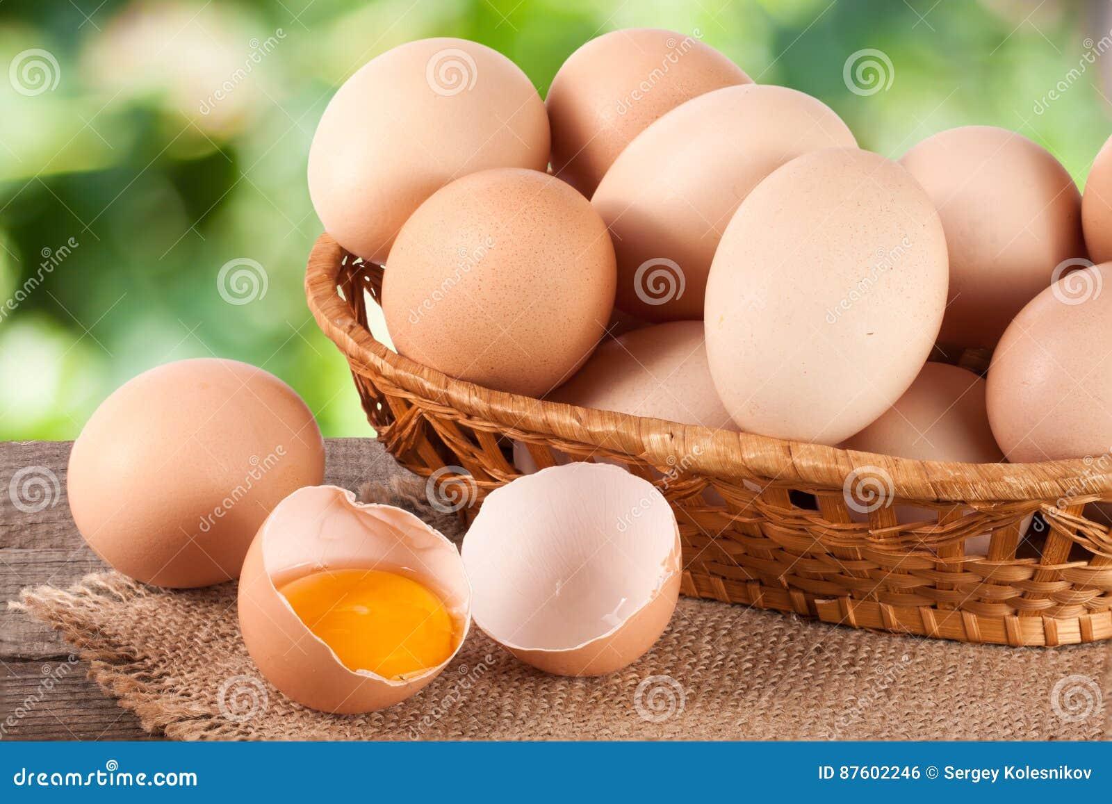 Ovos em uma cesta de vime em uma placa de madeira com fundo borrado do jardim
