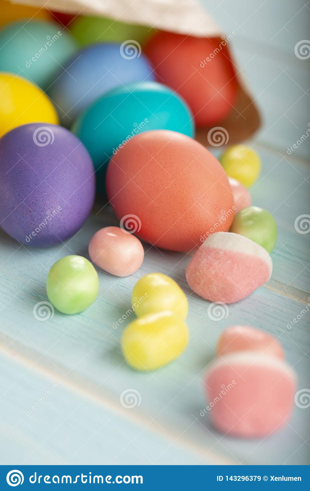 Ovos tingidos coloridos da galinha da Páscoa em um saco de papel e em doces