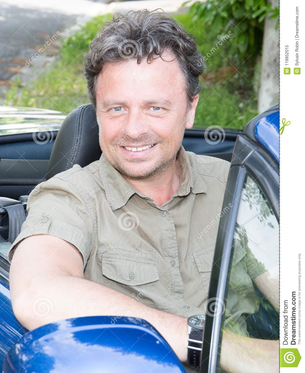 Owner Handsome man sitting in his newly bought cabriolet car looking out the window smiling