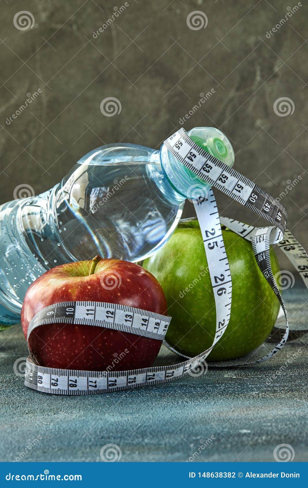 Owoc, butelka woda, metr na b??kicie z rozwodowym t?em