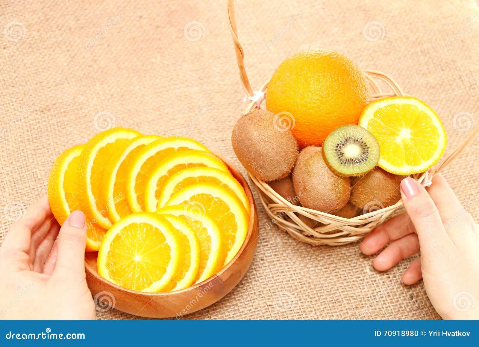 Owoc w pucharze trzyma ręki na naczyniach drewnianym koszu i,
