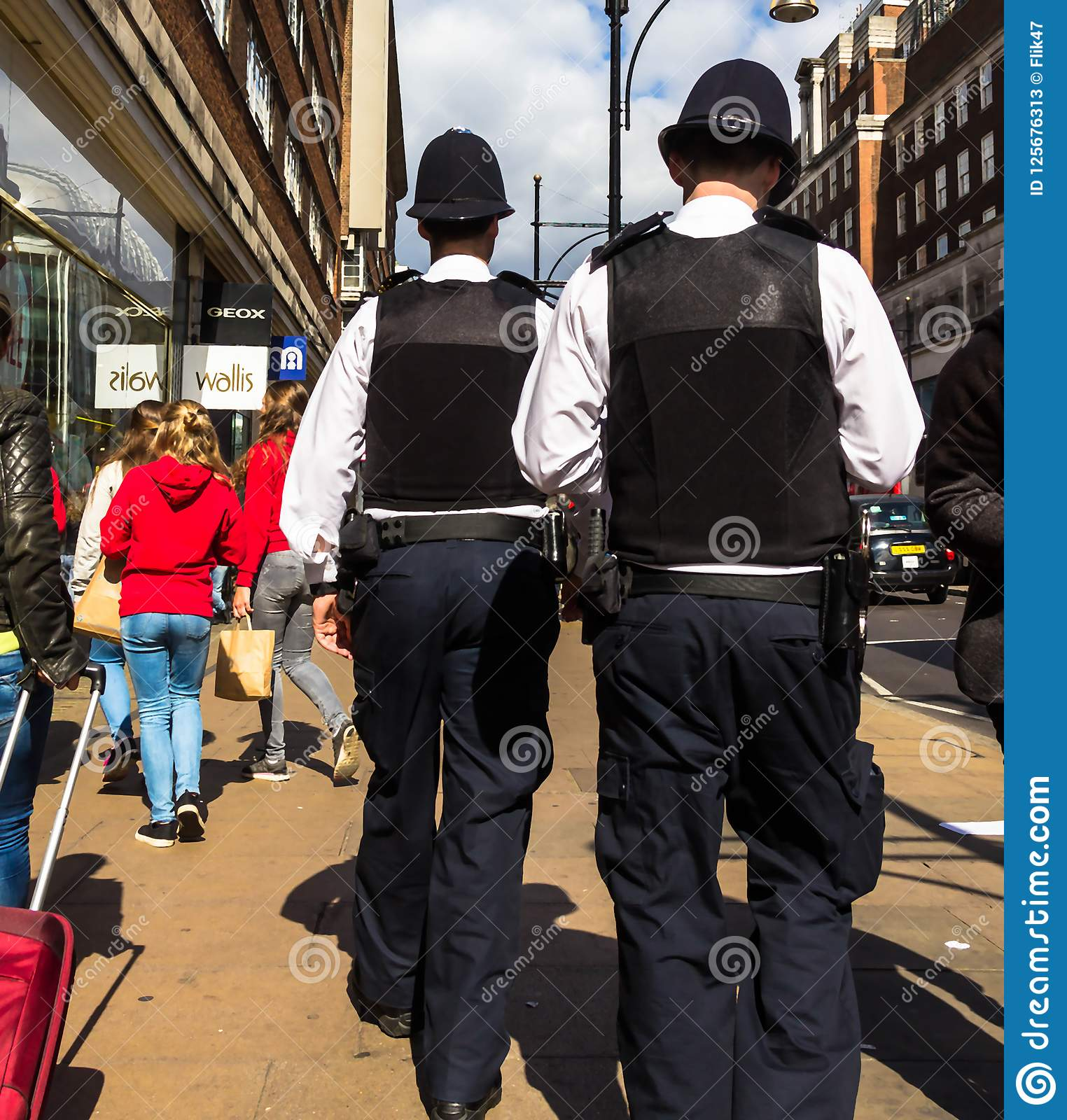 Oxford Street. Two unrecognizable police officers patrolling in the city.