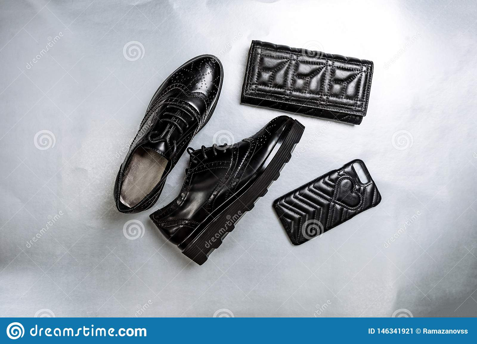 Oxfords perfor?s noirs de chaussures, une bourse et un cas de t?l?phone sur un fond blanc de papier