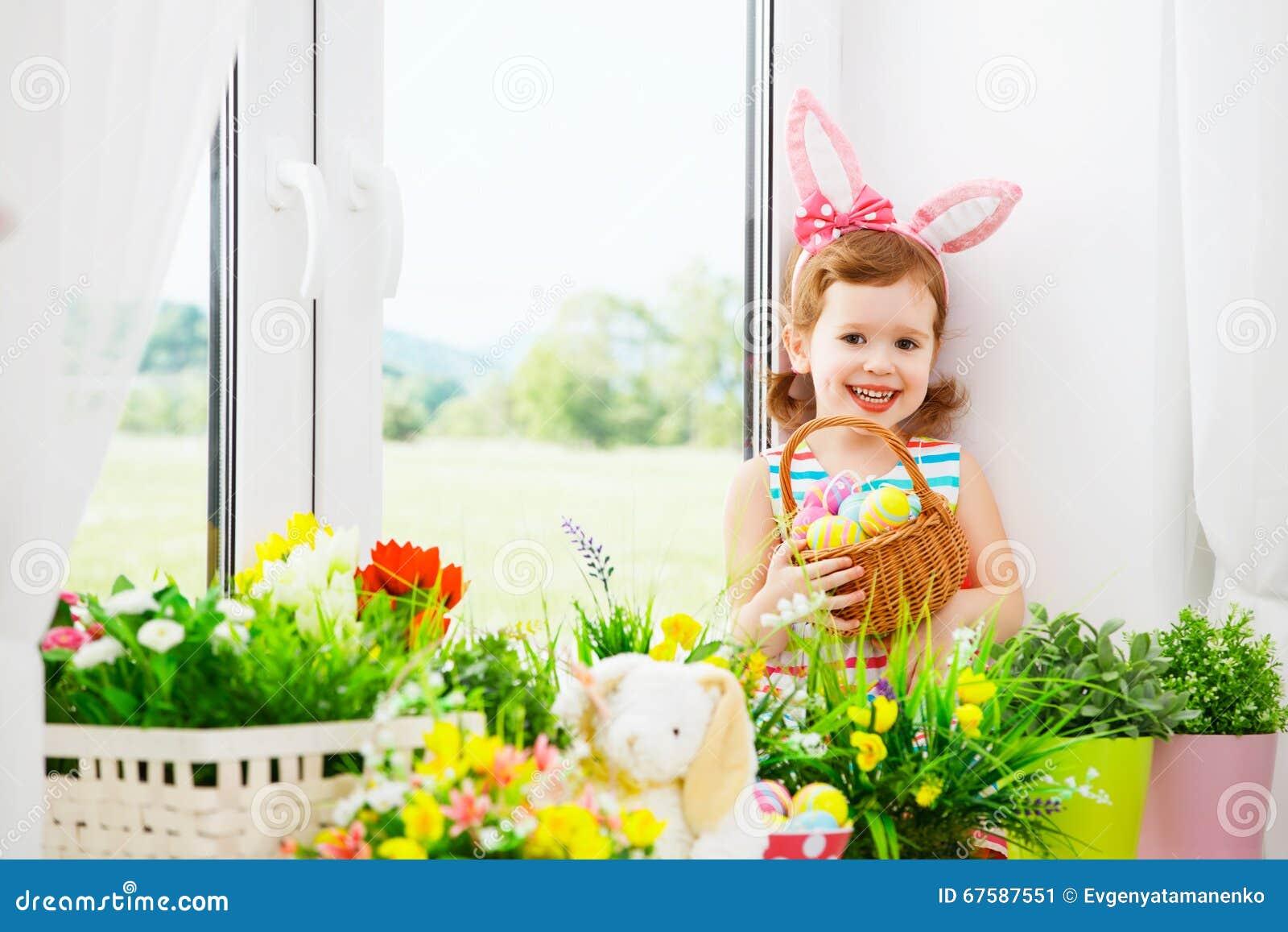Páscoa menina feliz da criança com orelhas do coelho e o sitti colorido dos ovos