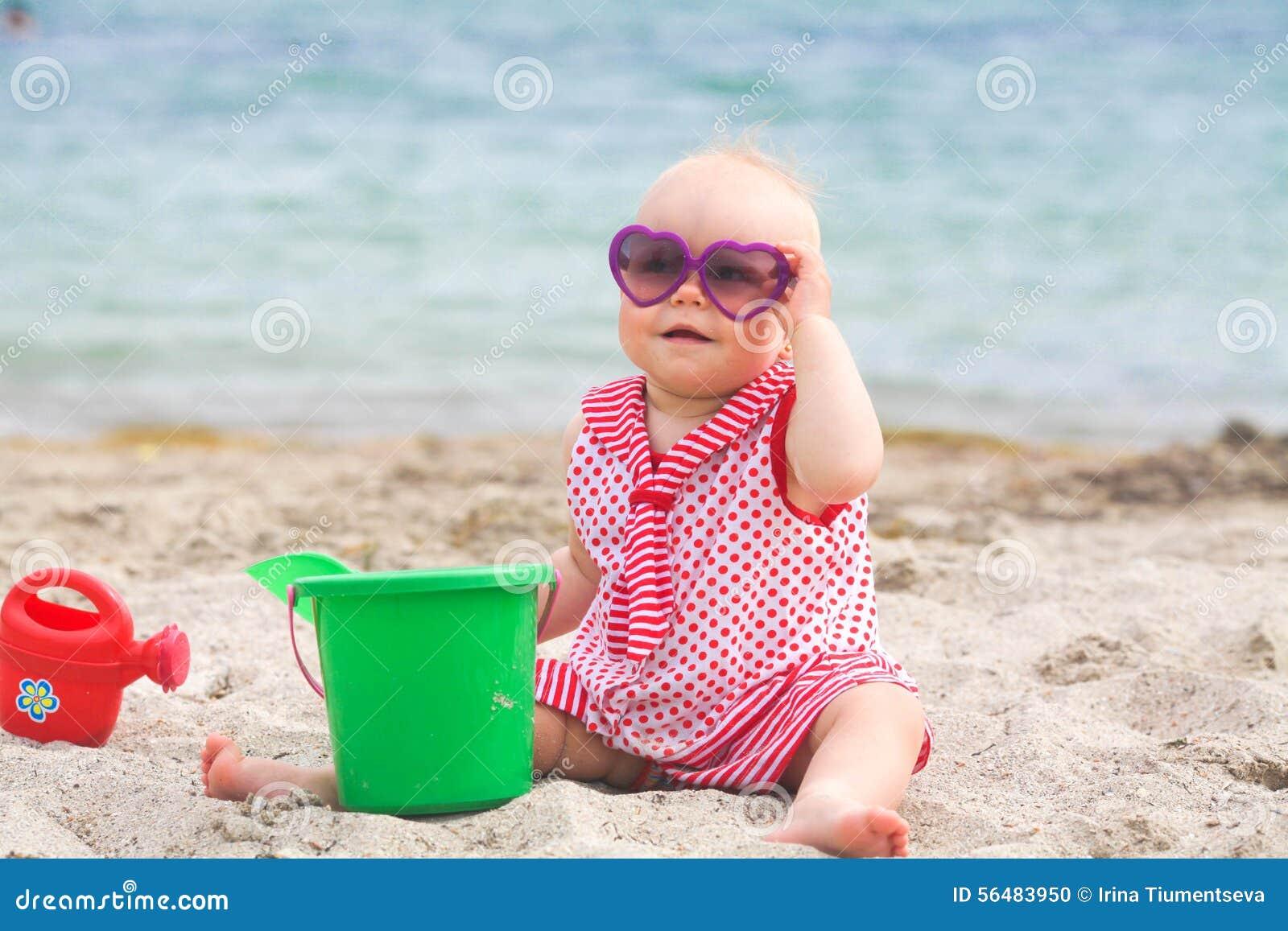 Pâté de sable de bâtiment de petite fille sur la plage tropicale d été