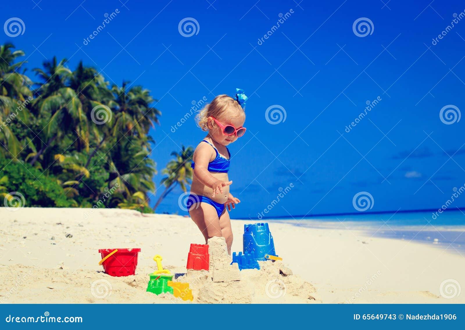 Pâté de sable mignon de bâtiment de petite fille sur la plage
