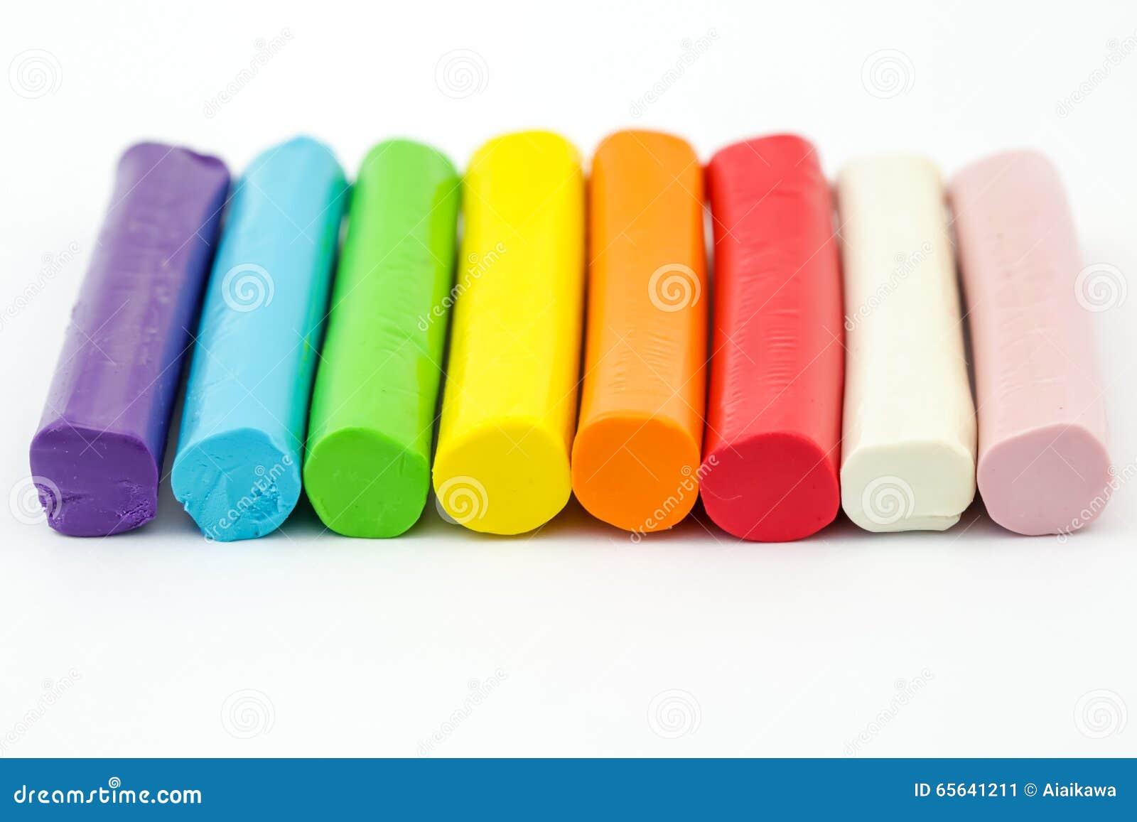 Pâte à modeler colorée de tige arrangeant sur le fond blanc