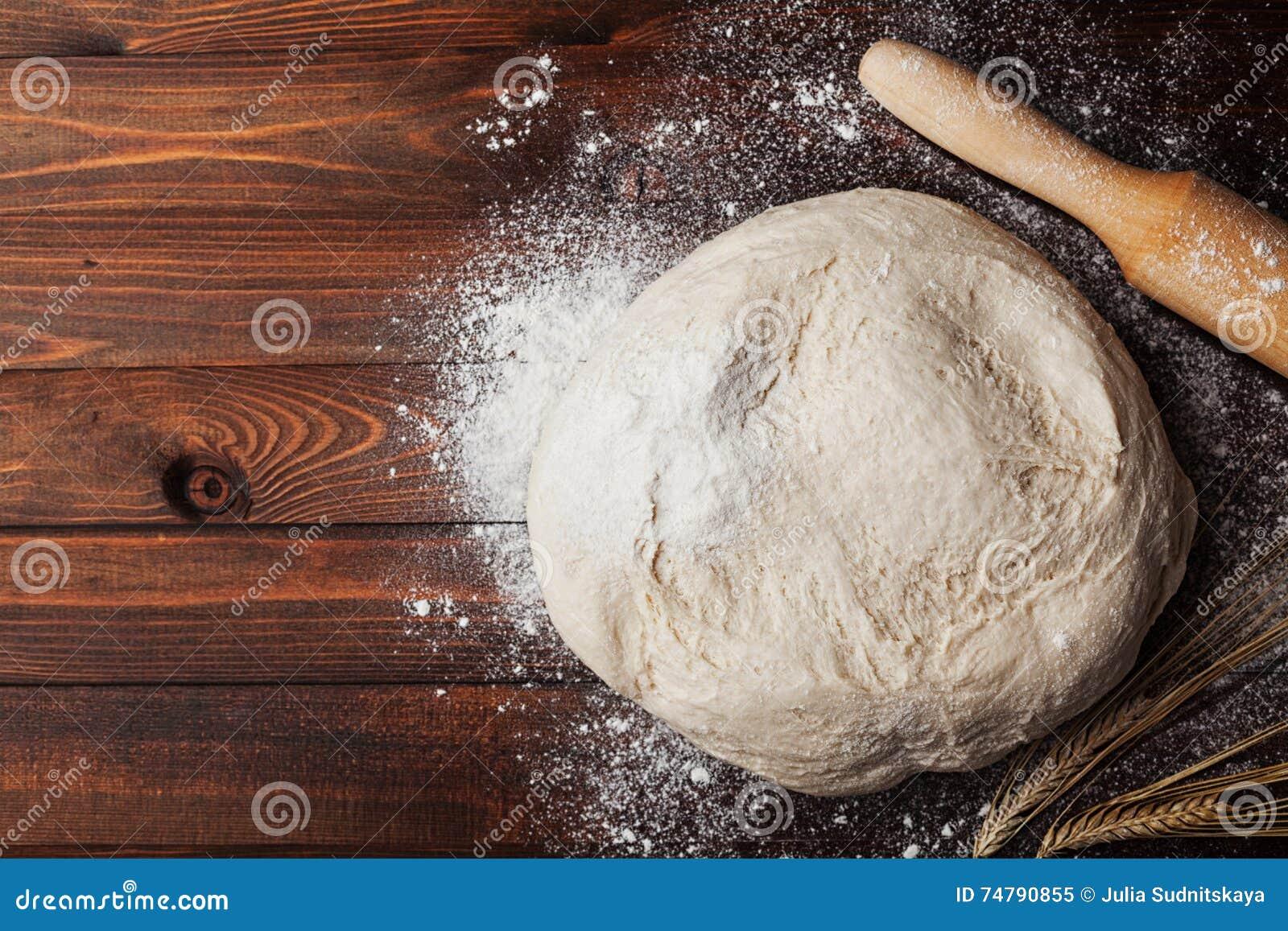 Pâte avec de la farine, goupille, oreilles de blé sur la table en bois rustique d en haut Pâtisserie faite maison pour le pain ou