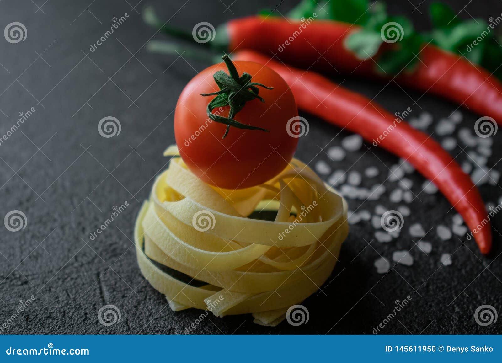 Pâtes crues de fettuccine avec la tomate fraîche, les feuilles vertes de sel brut de mer du cilantro et les poivrons de piment