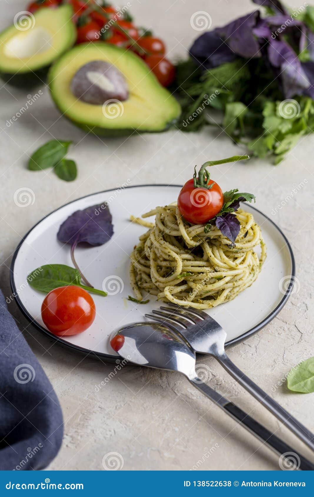 Pâtes italiennes avec le pesto, les herbes et les tomates-cerises au plat blanc