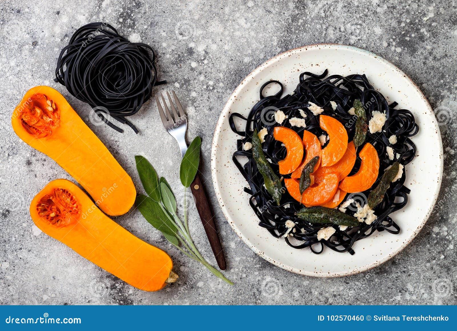 Pâtes noires avec la courge de butternut rôtie, le parmesan et la sauge frite Concept noir et orange de Halloween de partie de dî