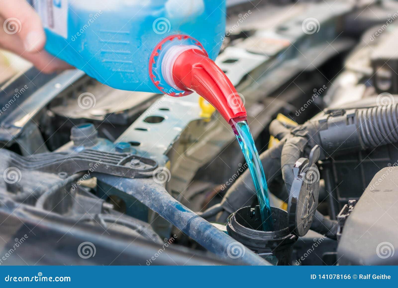 Påfyllning av vattenbehållaren med frostskyddsvätska i motorrummet av en bil