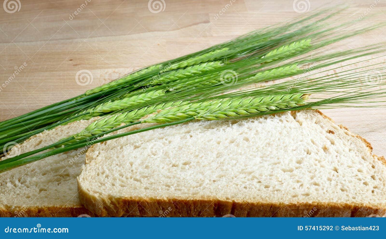 Pão branco com cevada da colheita no fundo de madeira