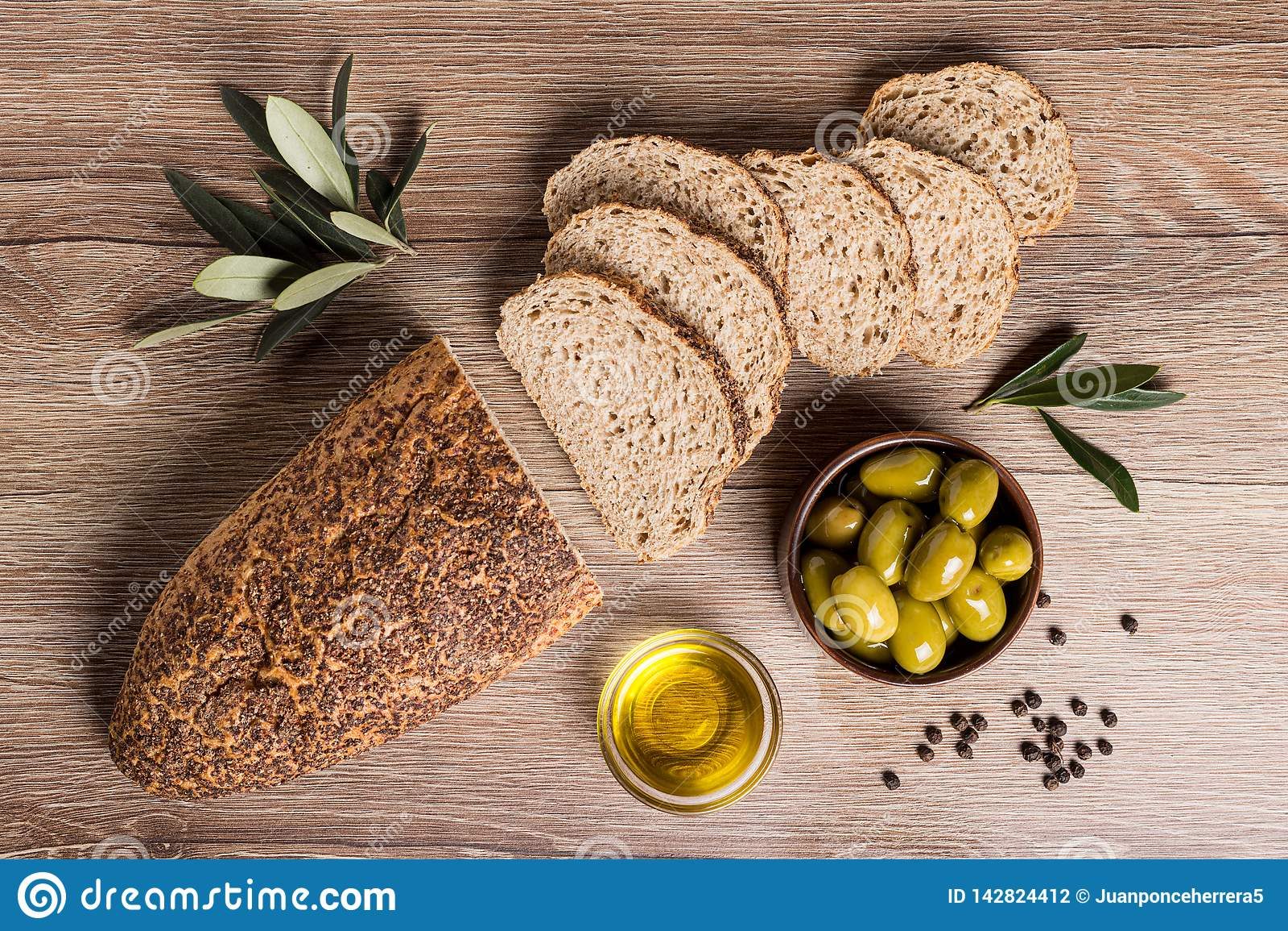 Pão do artesão com azeitonas e azeite em uma tabela de madeira