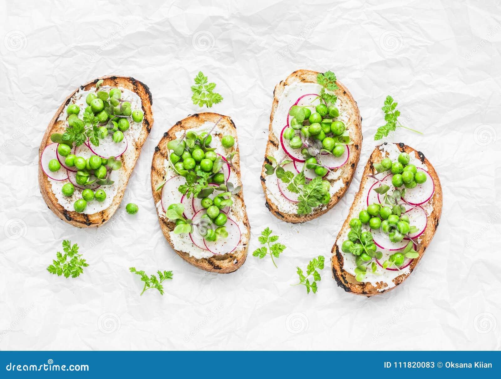 Pão grelhado, queijo macio, ervilhas verdes, rabanetes e micro sanduíches da mola dos verdes Comer saudável, emagrecimento, estil