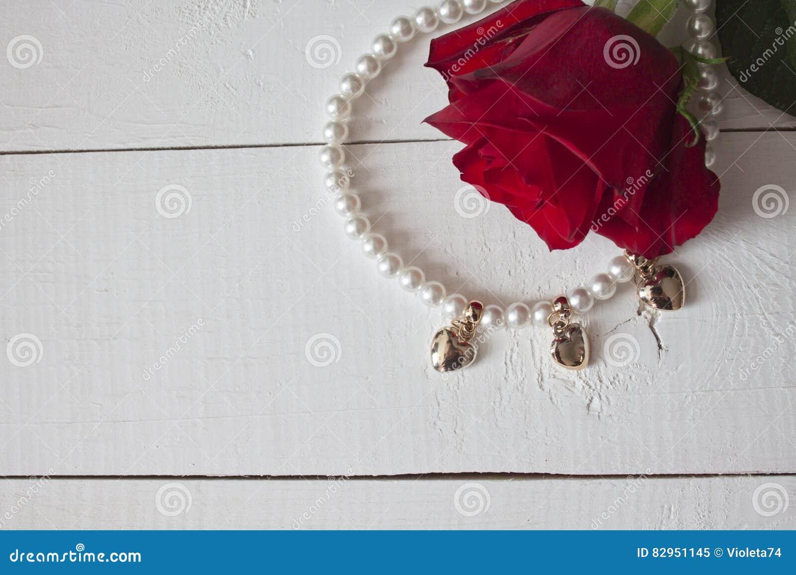 Pärlemorfärg halsband med guld- hjärtor på vitt trä