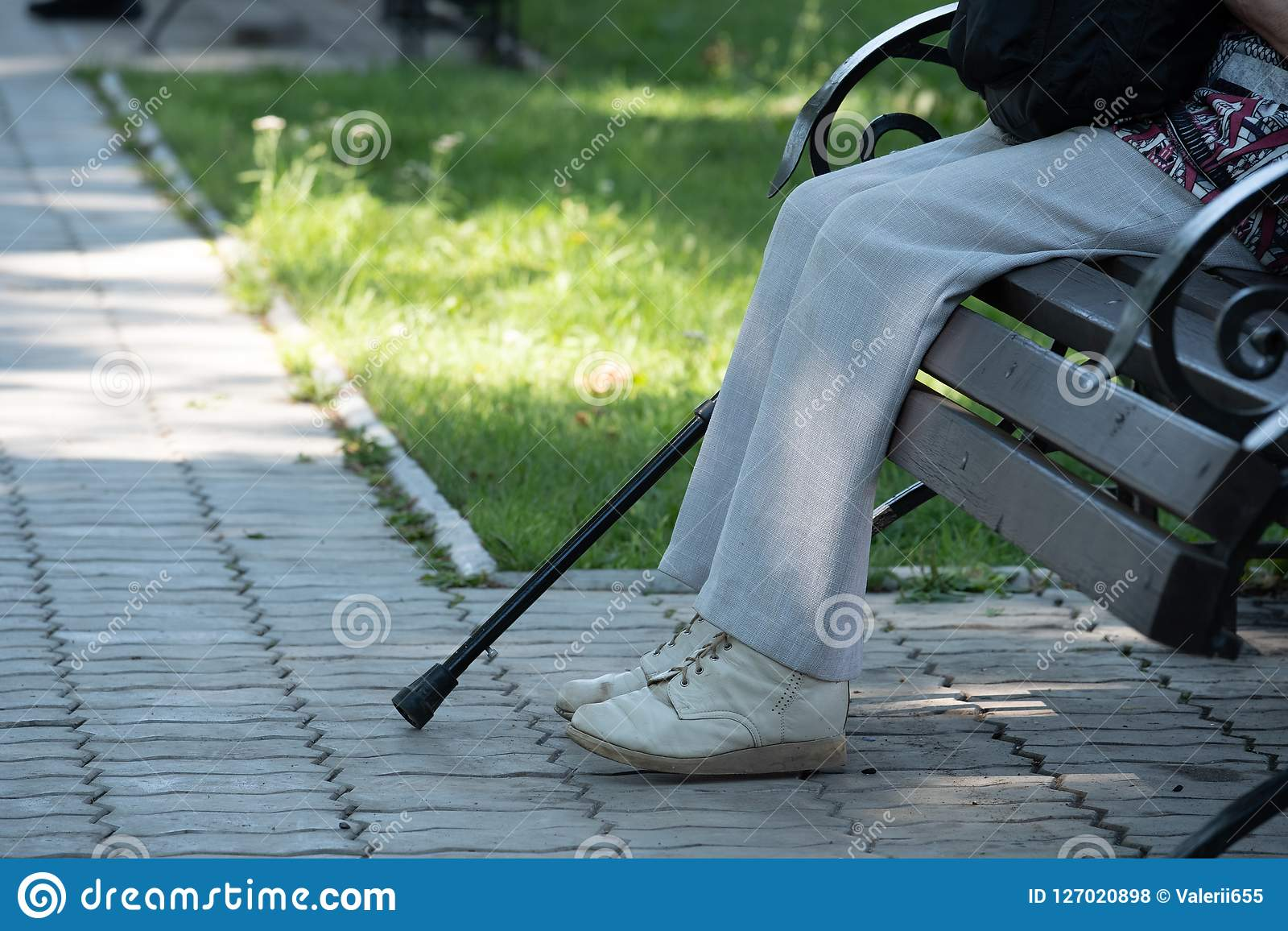 På bilden av en fot, en krycka och en bänk i parkera
