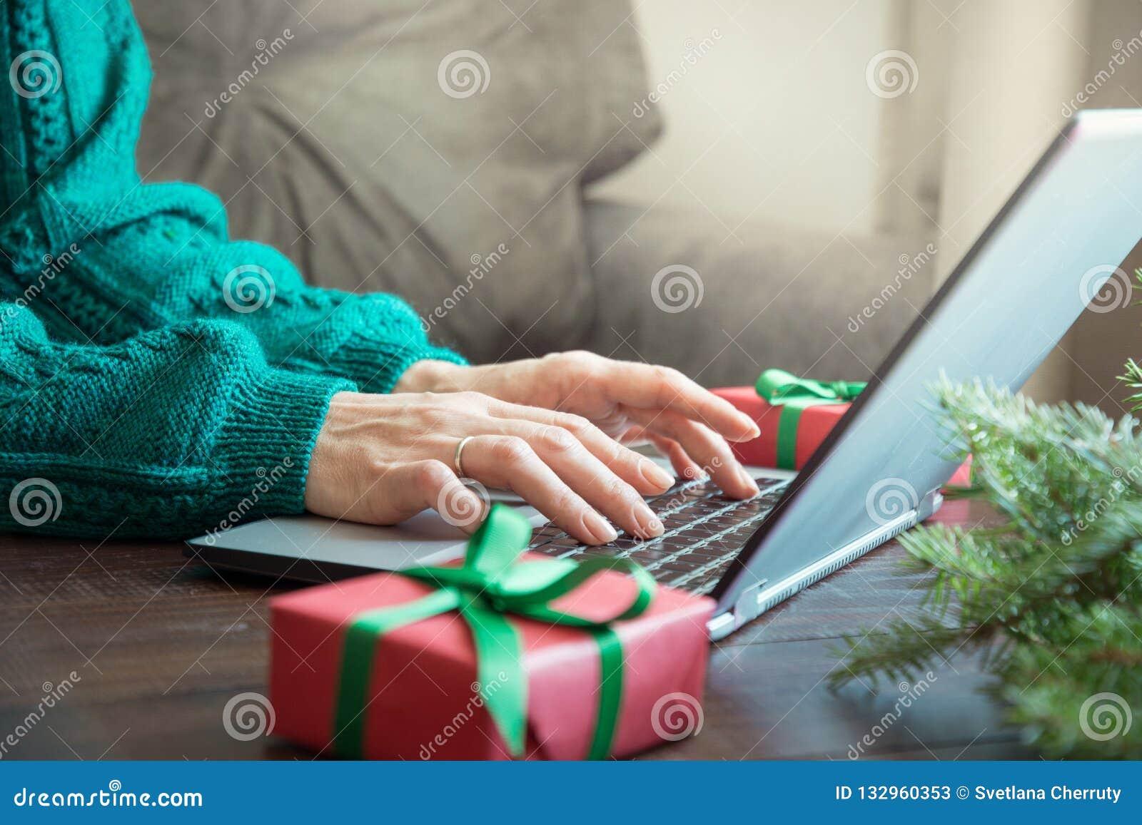På bokstäver som hänger julklockor Kvinna som skriver på bärbara datorn i hemmiljö Xmas-begrepp Hyvla ferier