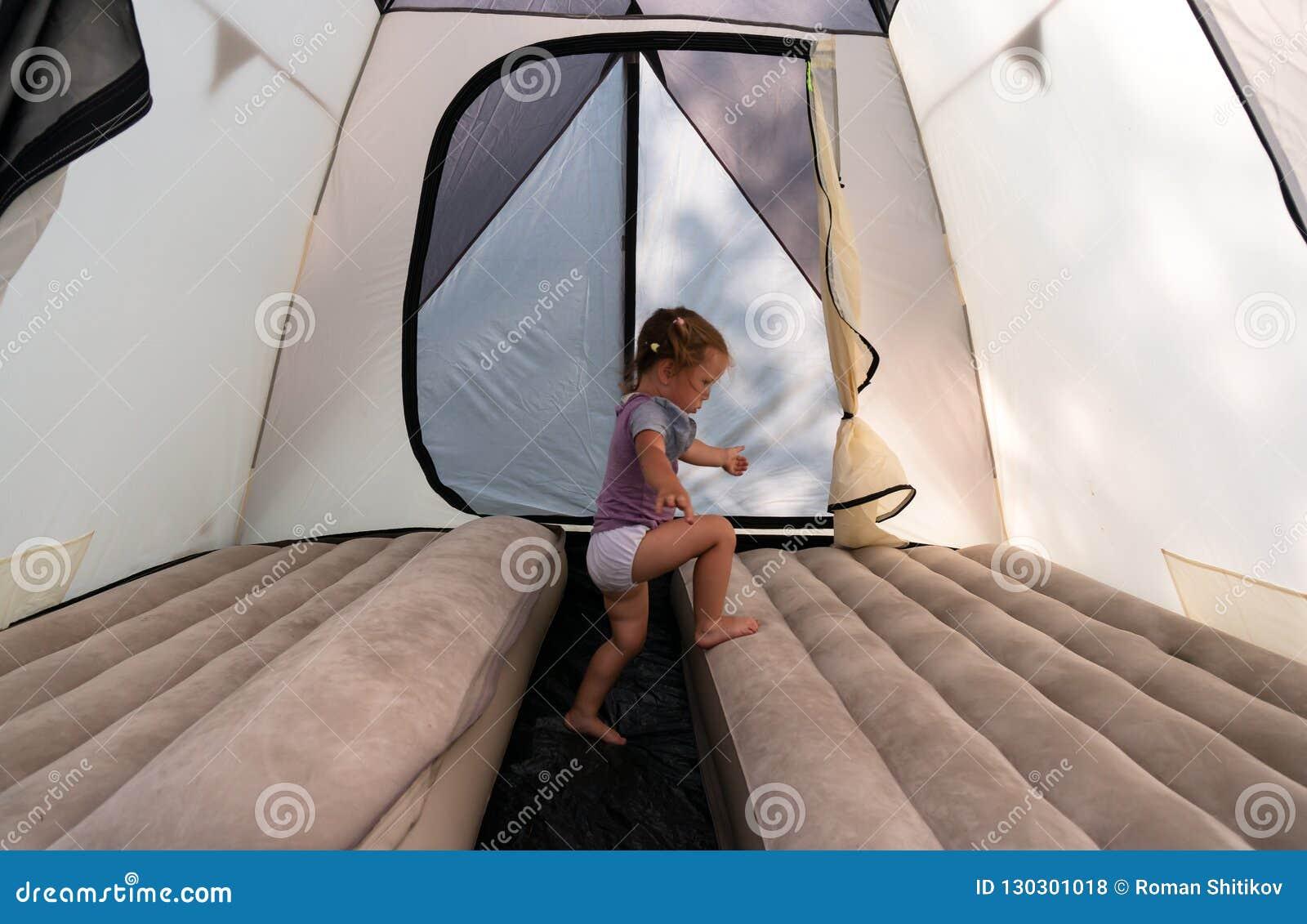 På campingplatsen lite flicka i hopp för ett tält på madrasser