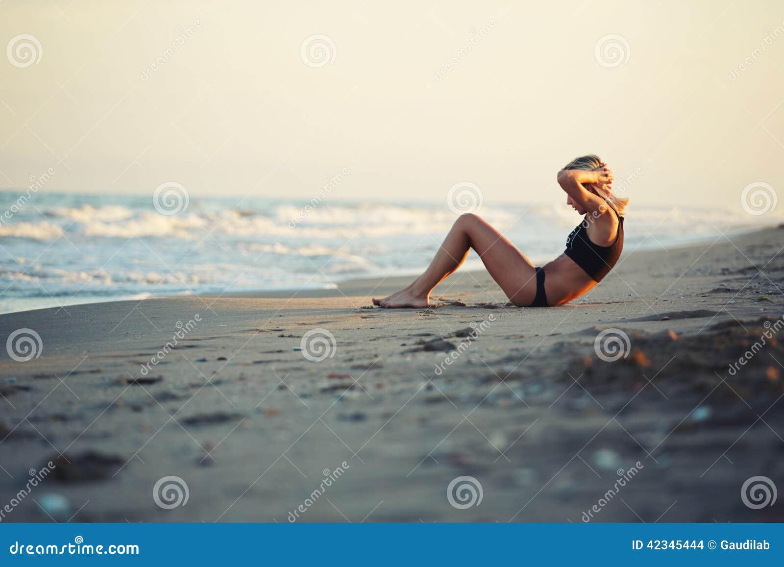 På den fantastiska solnedgångunga flickan som gör övningar på stranden