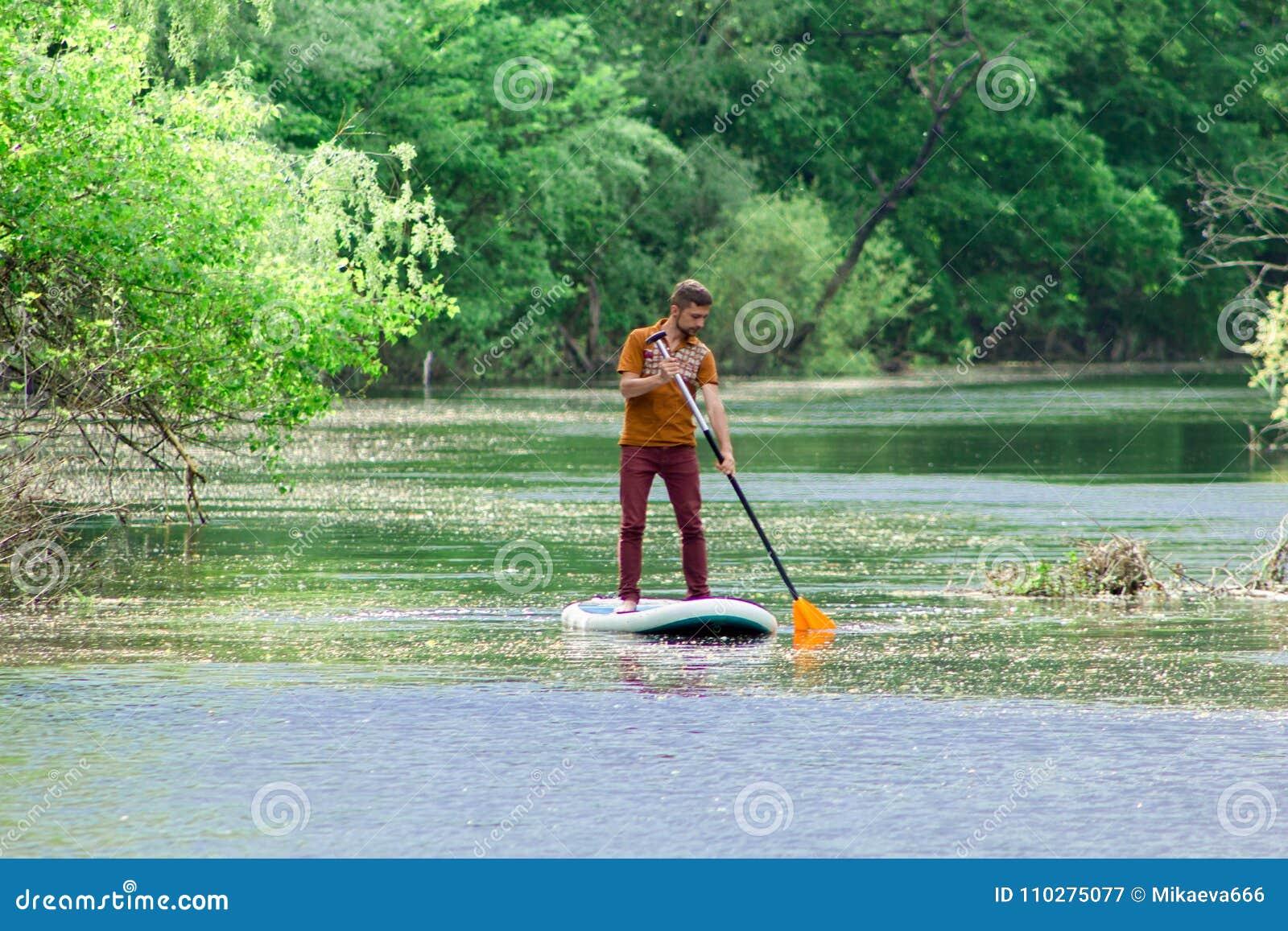 På floden i avståndet simmar en man på ett supbräde
