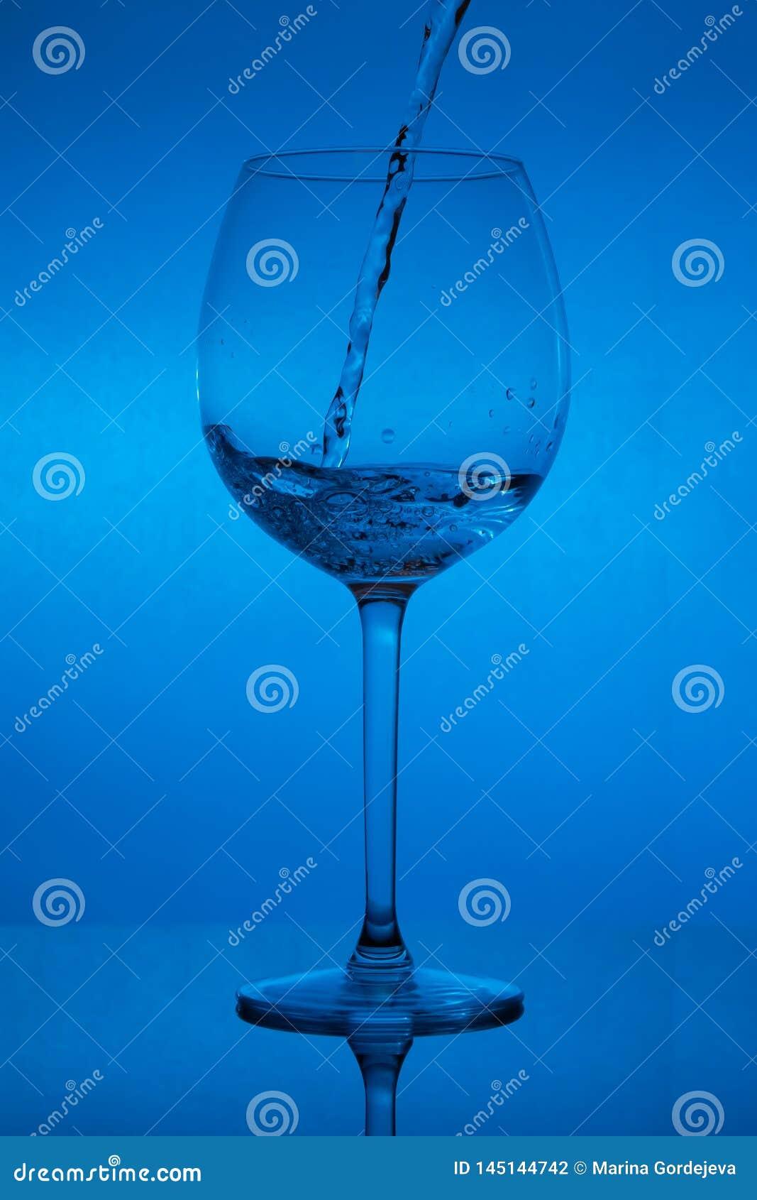 Påfyllning av exponeringsglaset, hällande vinglas på blå bakgrund