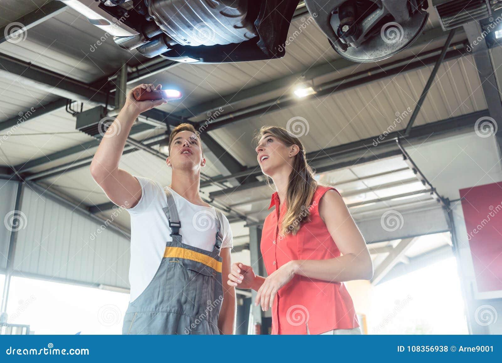 Pålitlig auto mekaniker som kontrollerar bilen av en kvinna i ett modernt a