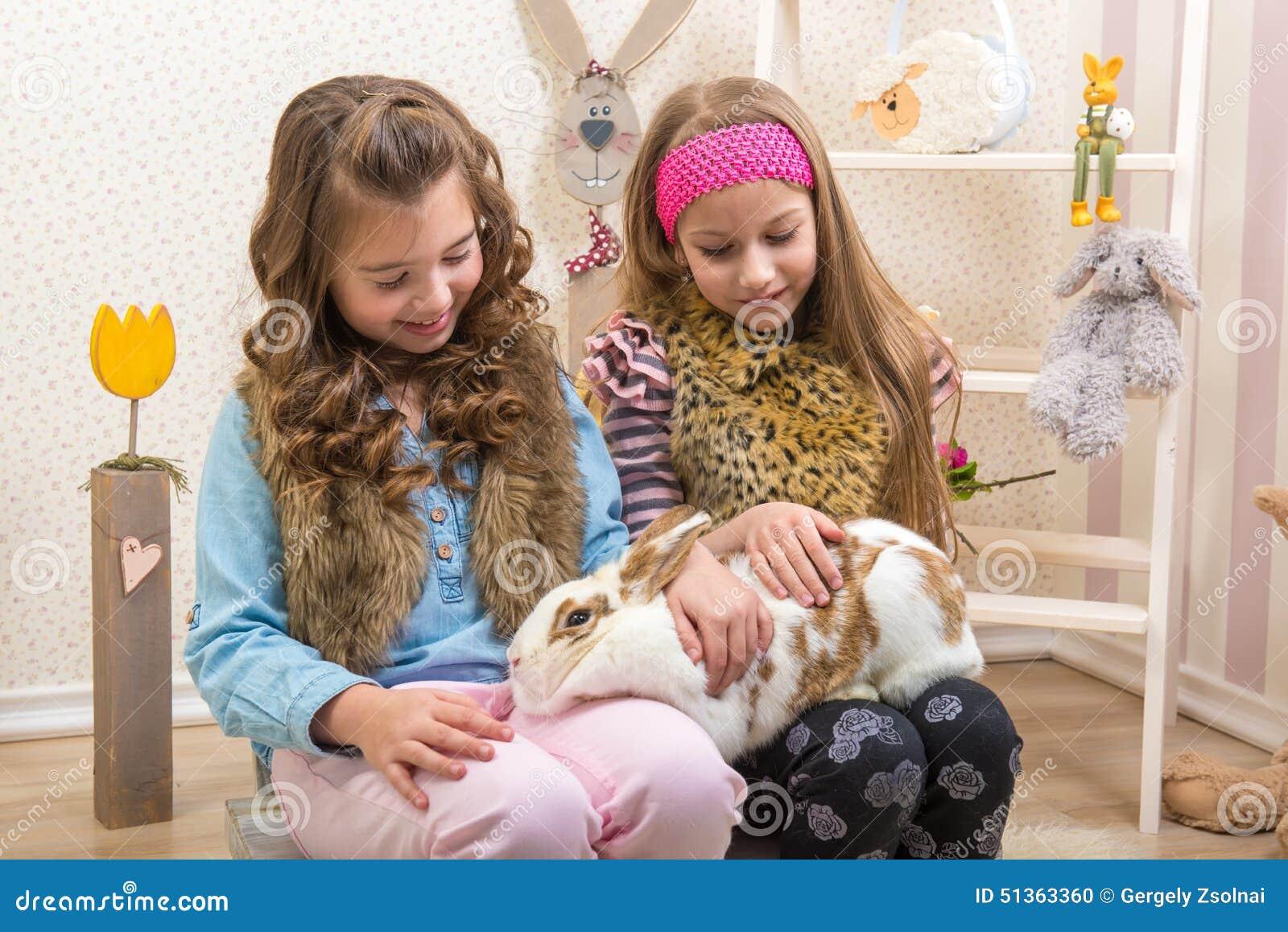 Påsk - små flickor som slår den enorma levande kaninen
