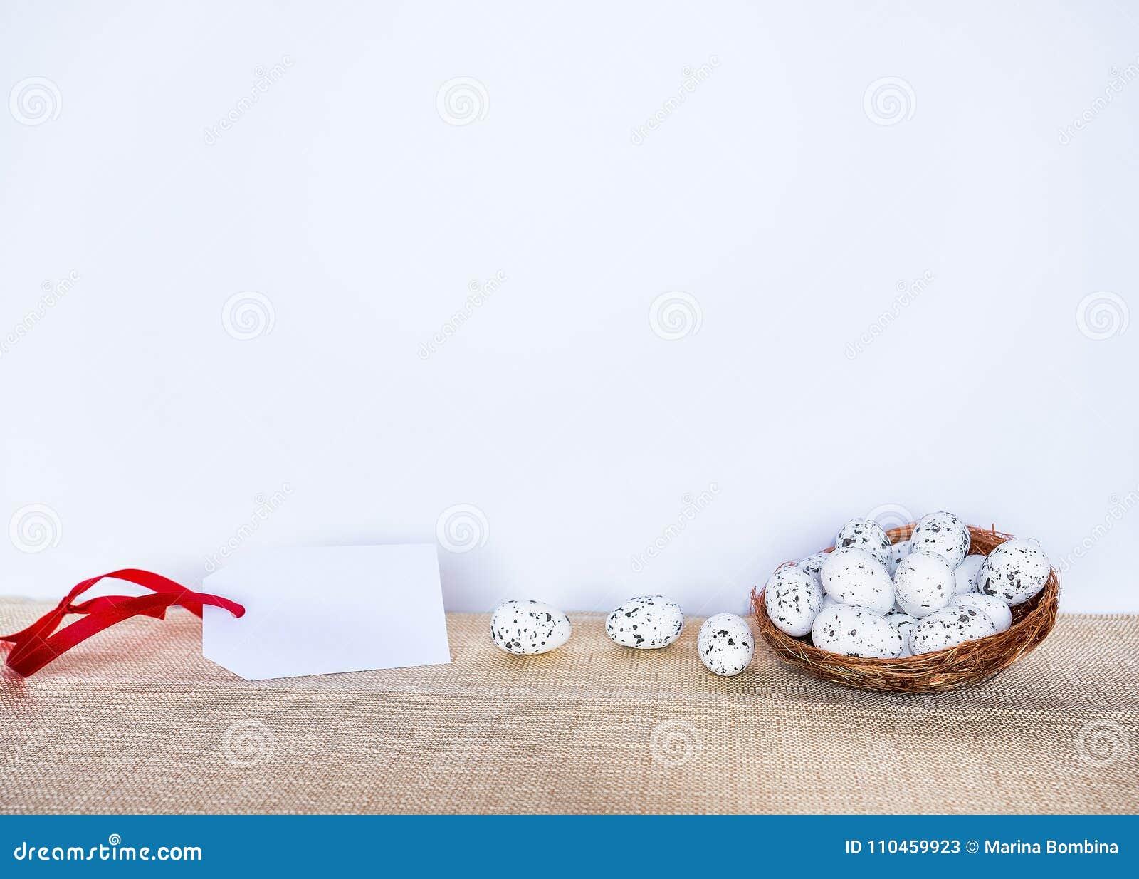 Påskbakgrund med ägg i fågelrede och den tomma gåvan märker tecknet