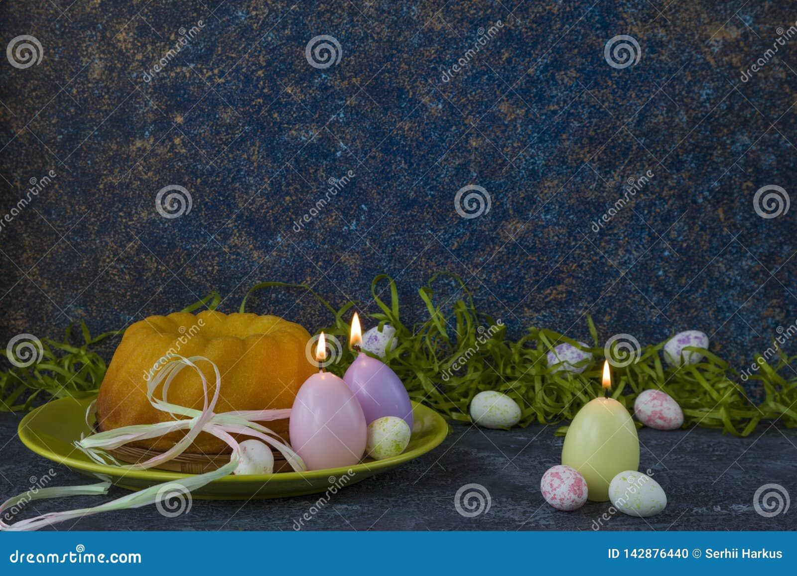 Påskbröd på den gröna plattan och målade tabellen för sten för mörker för jon för påskägg som dekoreras med grönt gräs