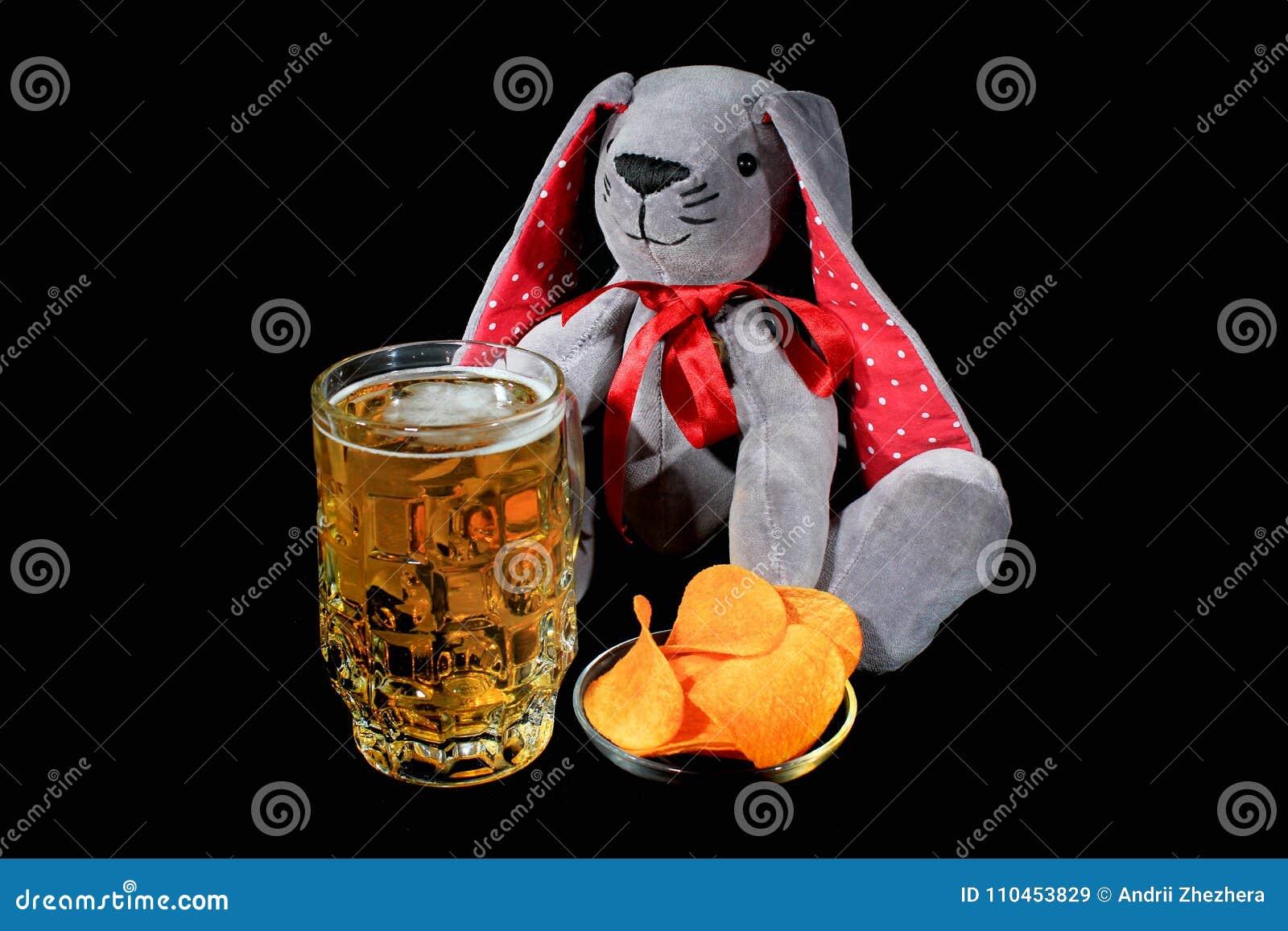 Påskkaninen med rånar av öl- och potatischiper mot svart bakgrund