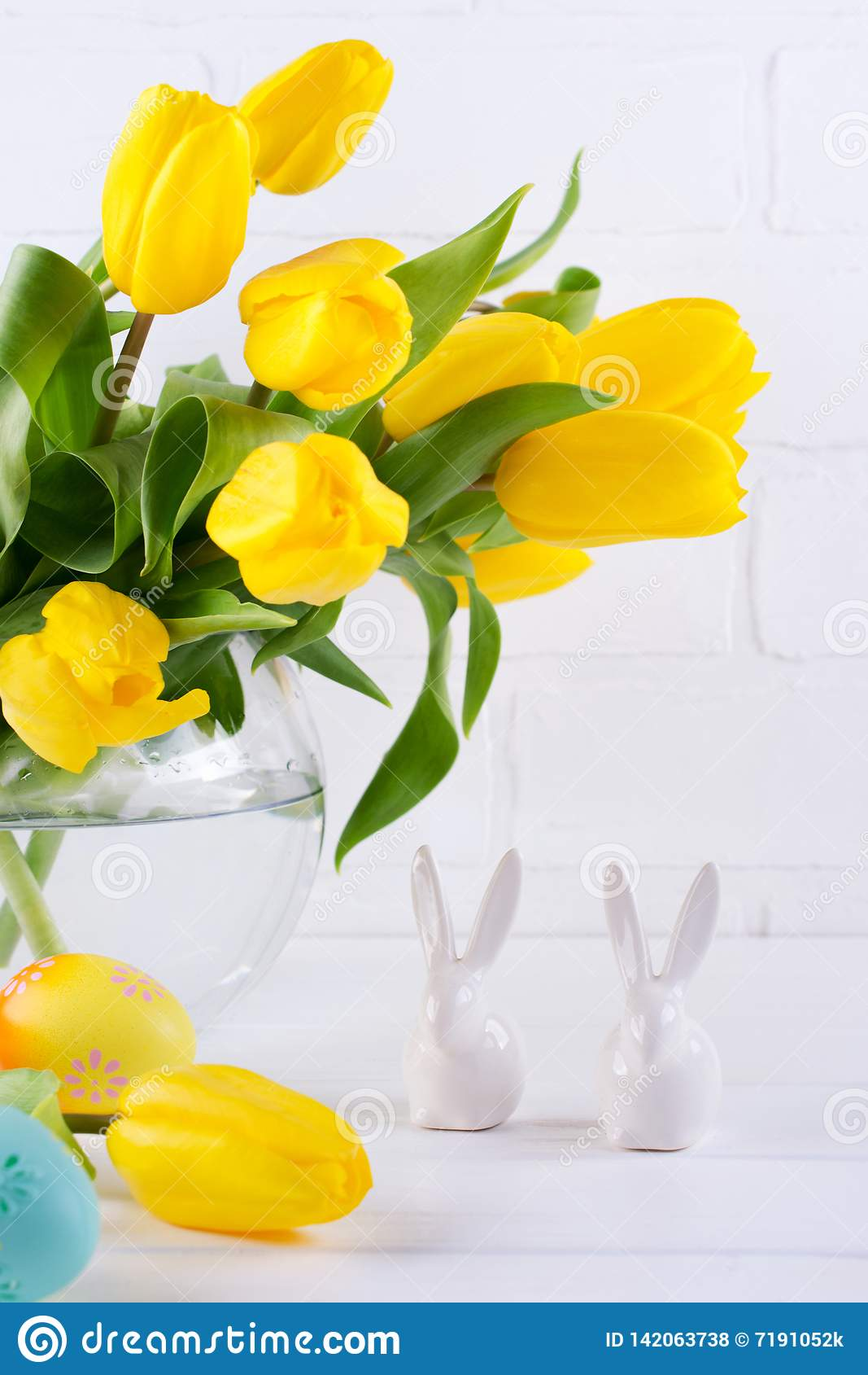 Påsksammansättning med buketten av gula tulpanblommor i exponeringsglasvas och två vita keramiska kaniner på vit