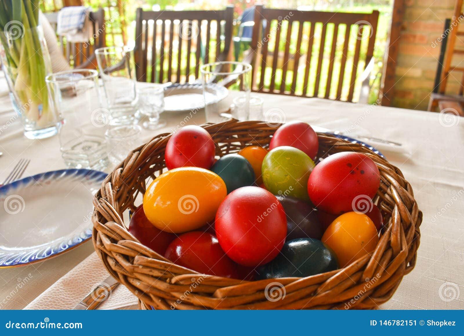 Påsktablewear som är utomhus- under pergolan med färgrika ägg i en solig dag