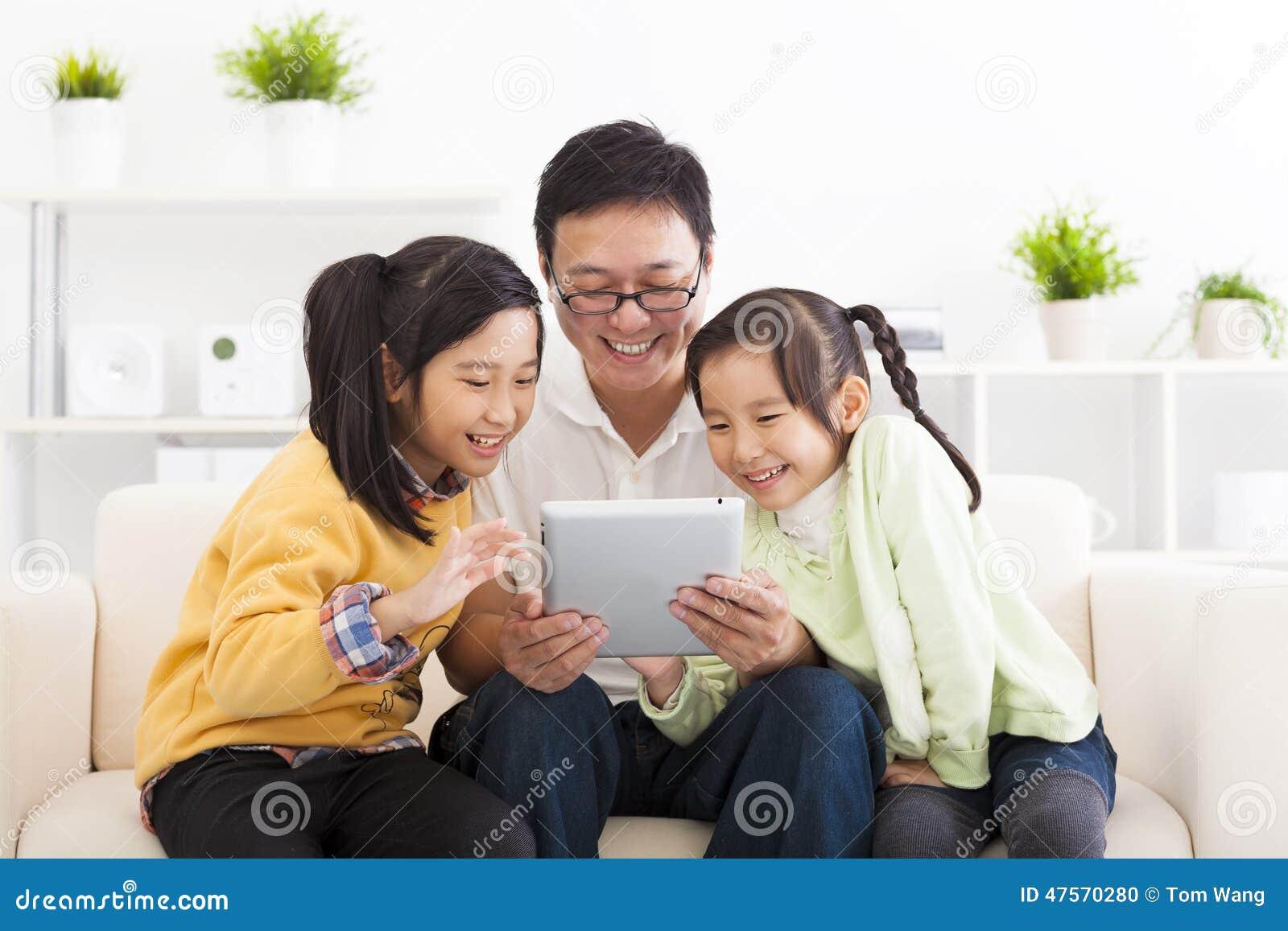 Père à l aide du PC de comprimé avec de petites filles