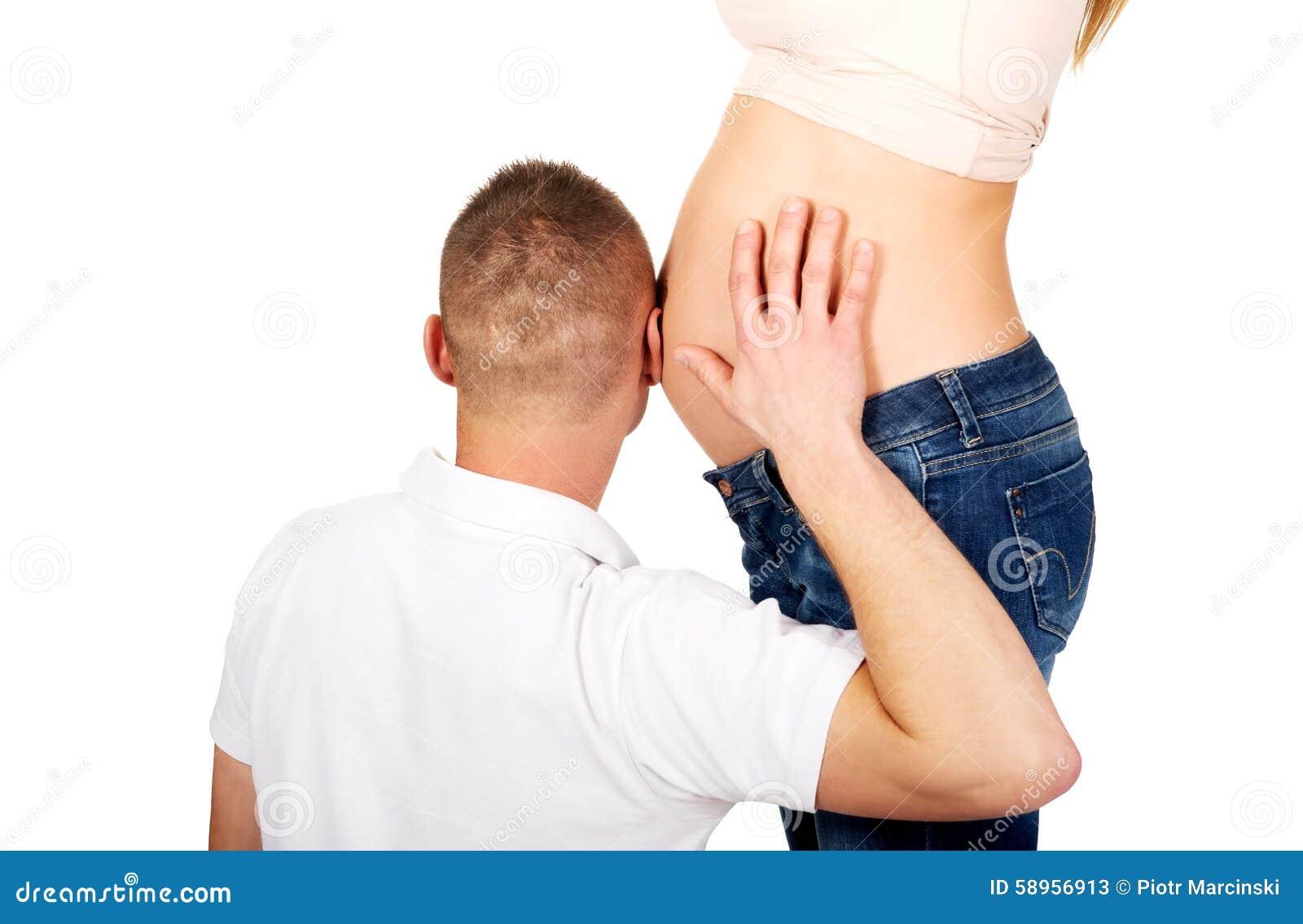 Père écoutant le ventre enceinte de la mère