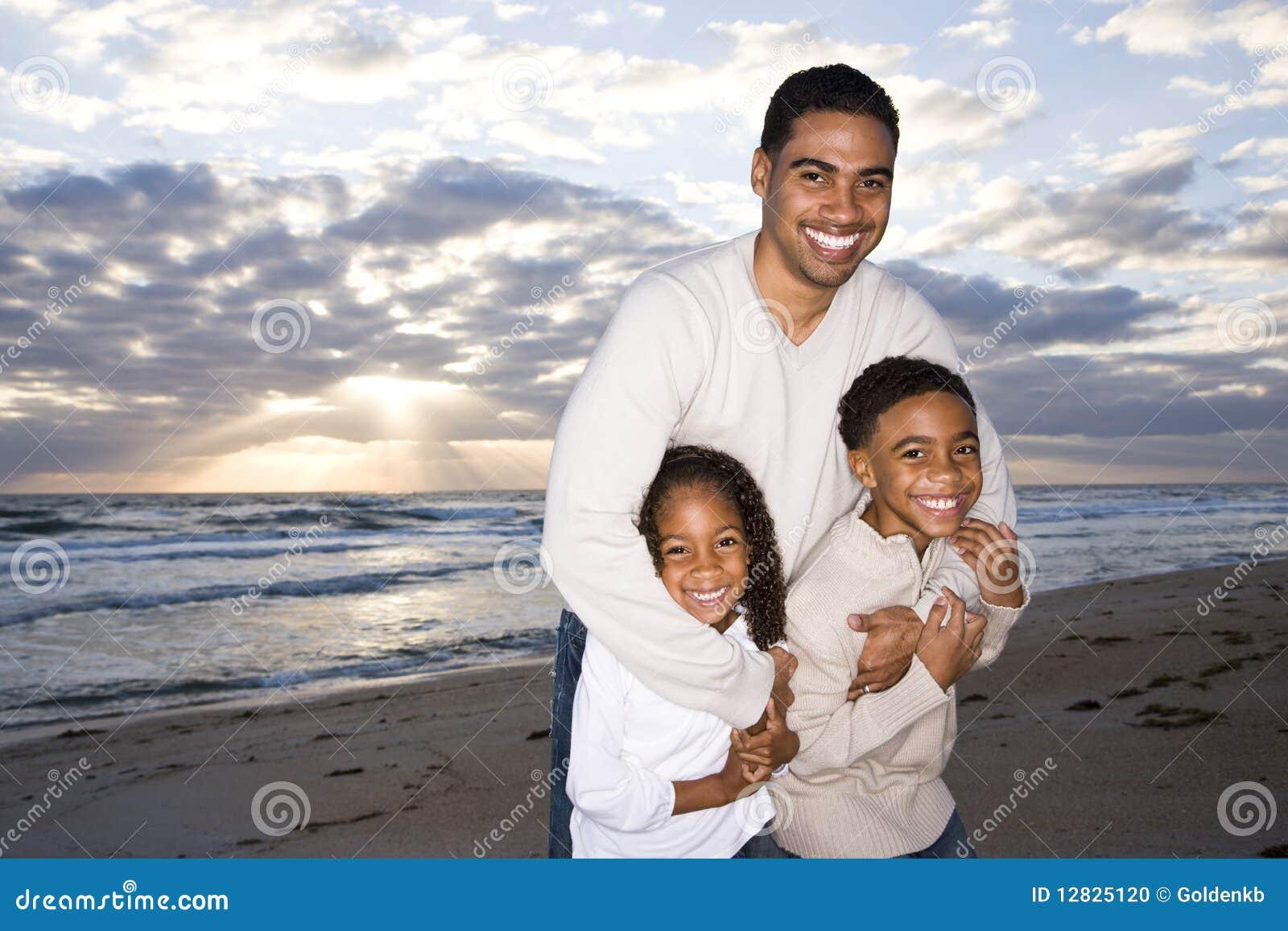 Père afro-américain et deux enfants sur la plage