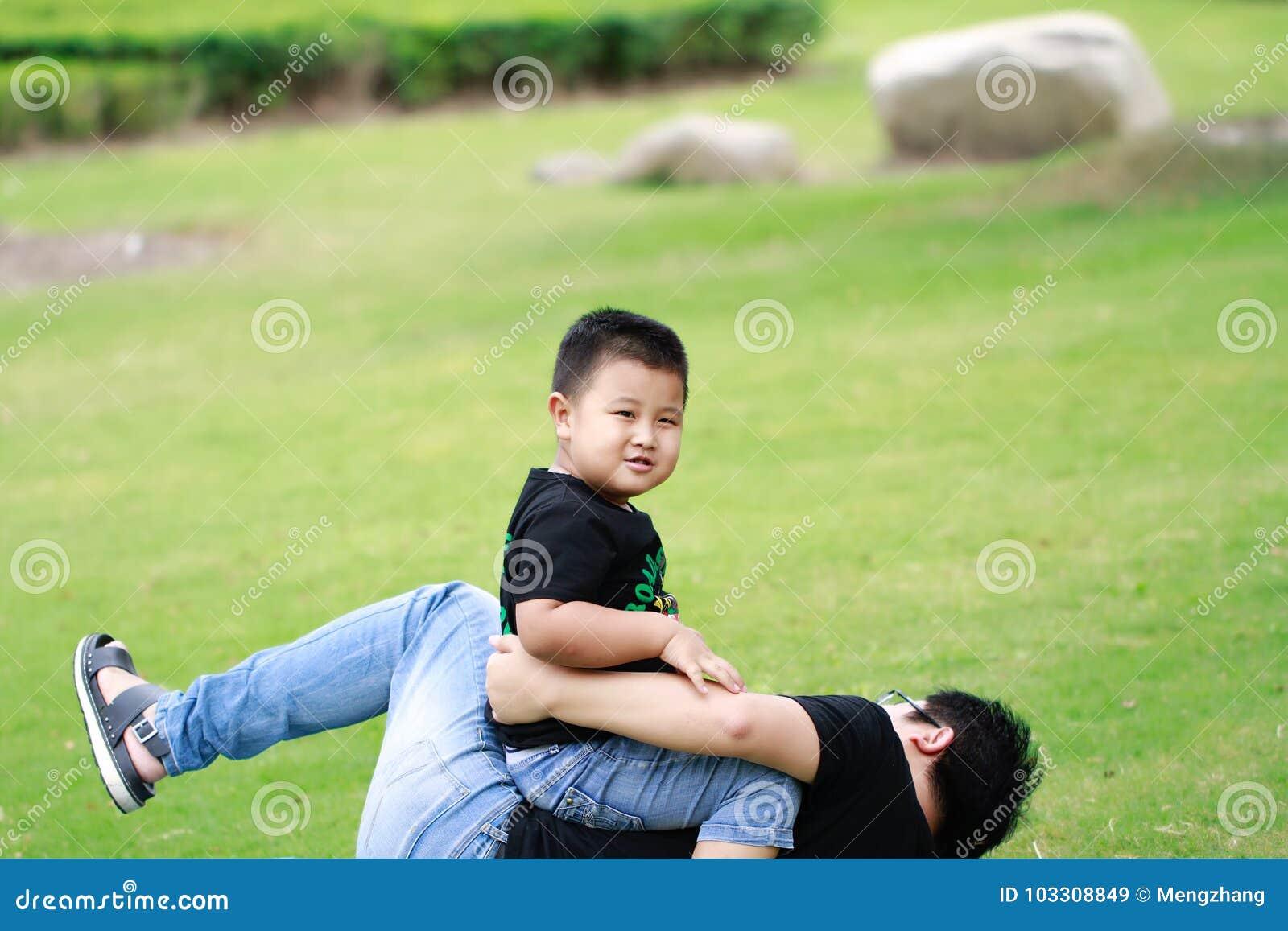 Père asiatique et fils ayant l amusement dans le stationnement