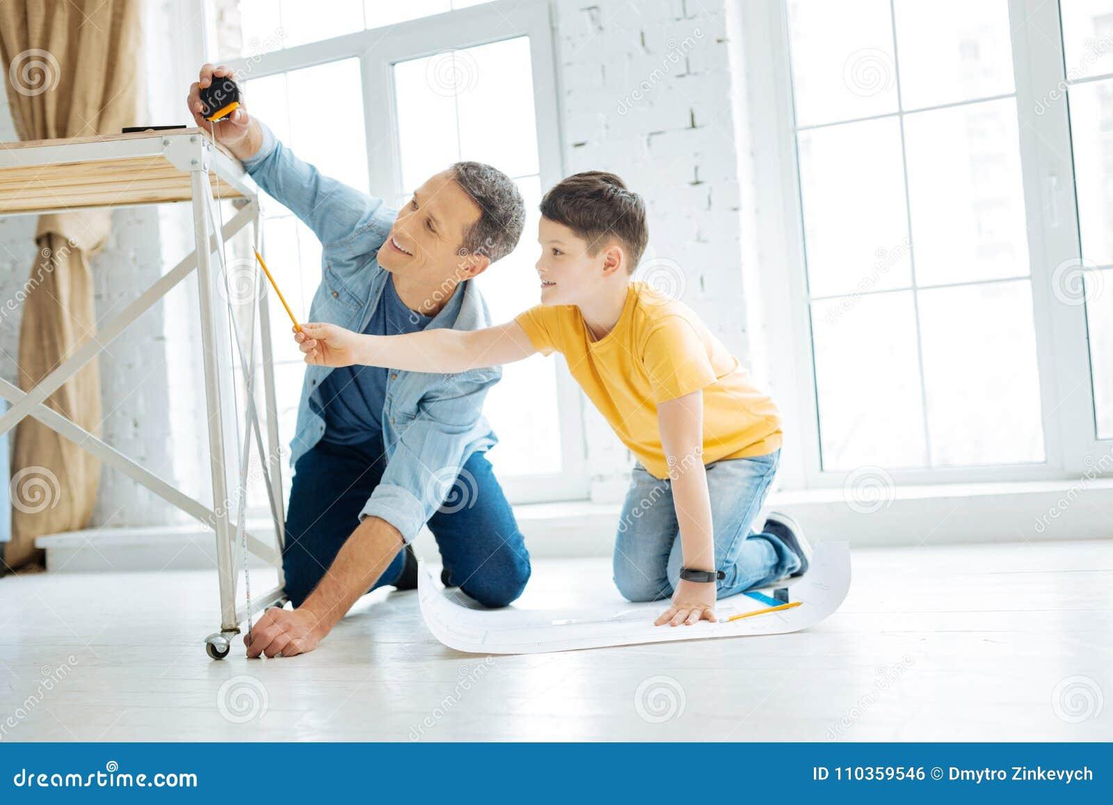 Père avec du charme et fils travaillant à la construction de table