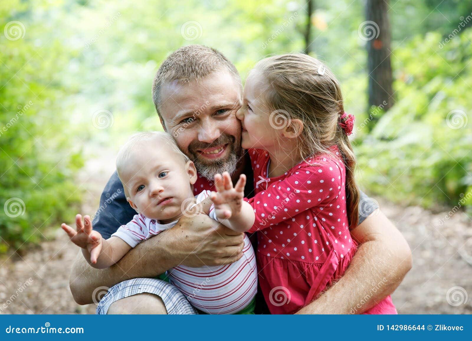 Père consacré étreignant son fils et fille, appréciant l extérieur