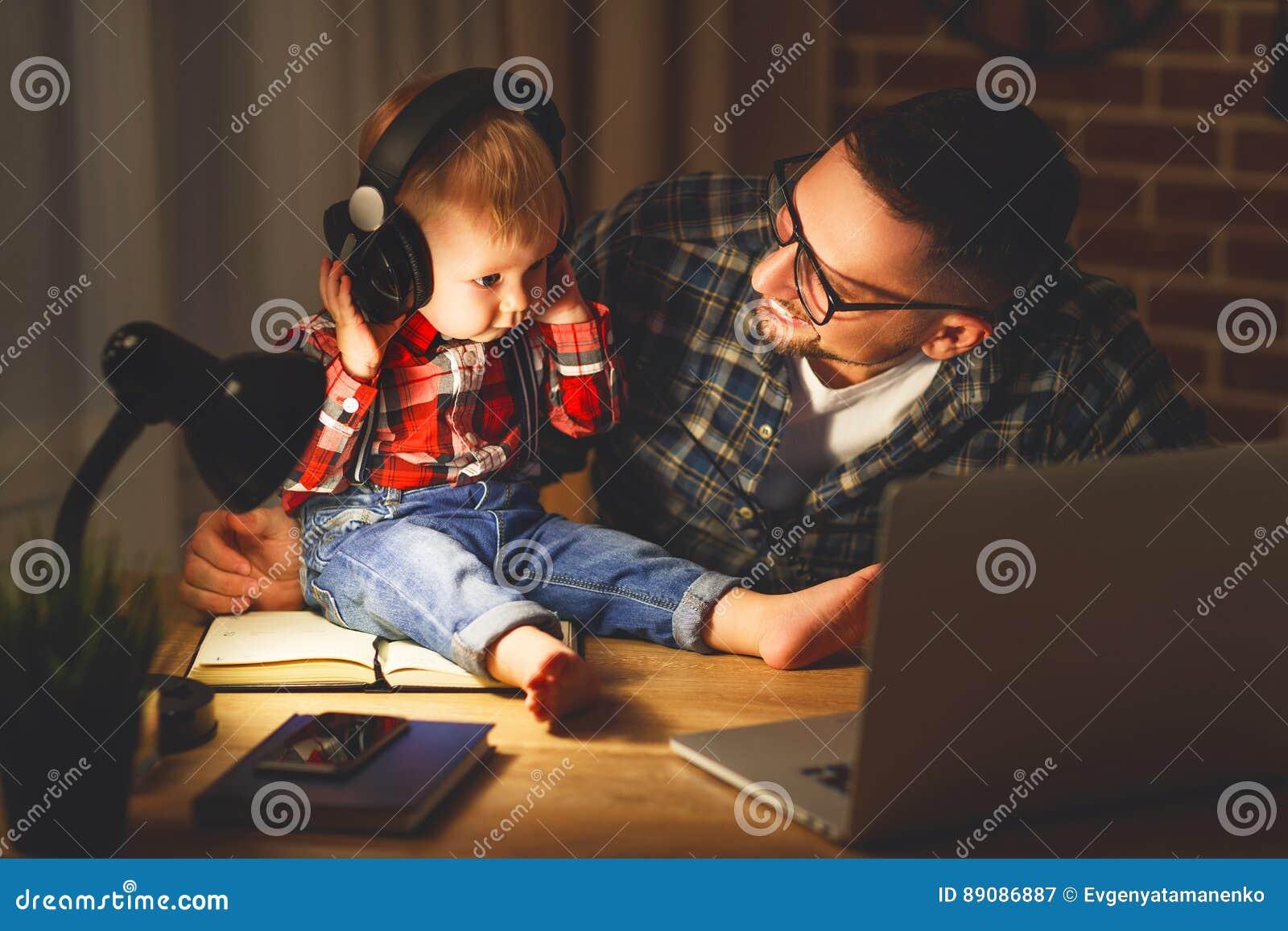 Père de famille et bébé de fils écoutant la musique avec des écouteurs