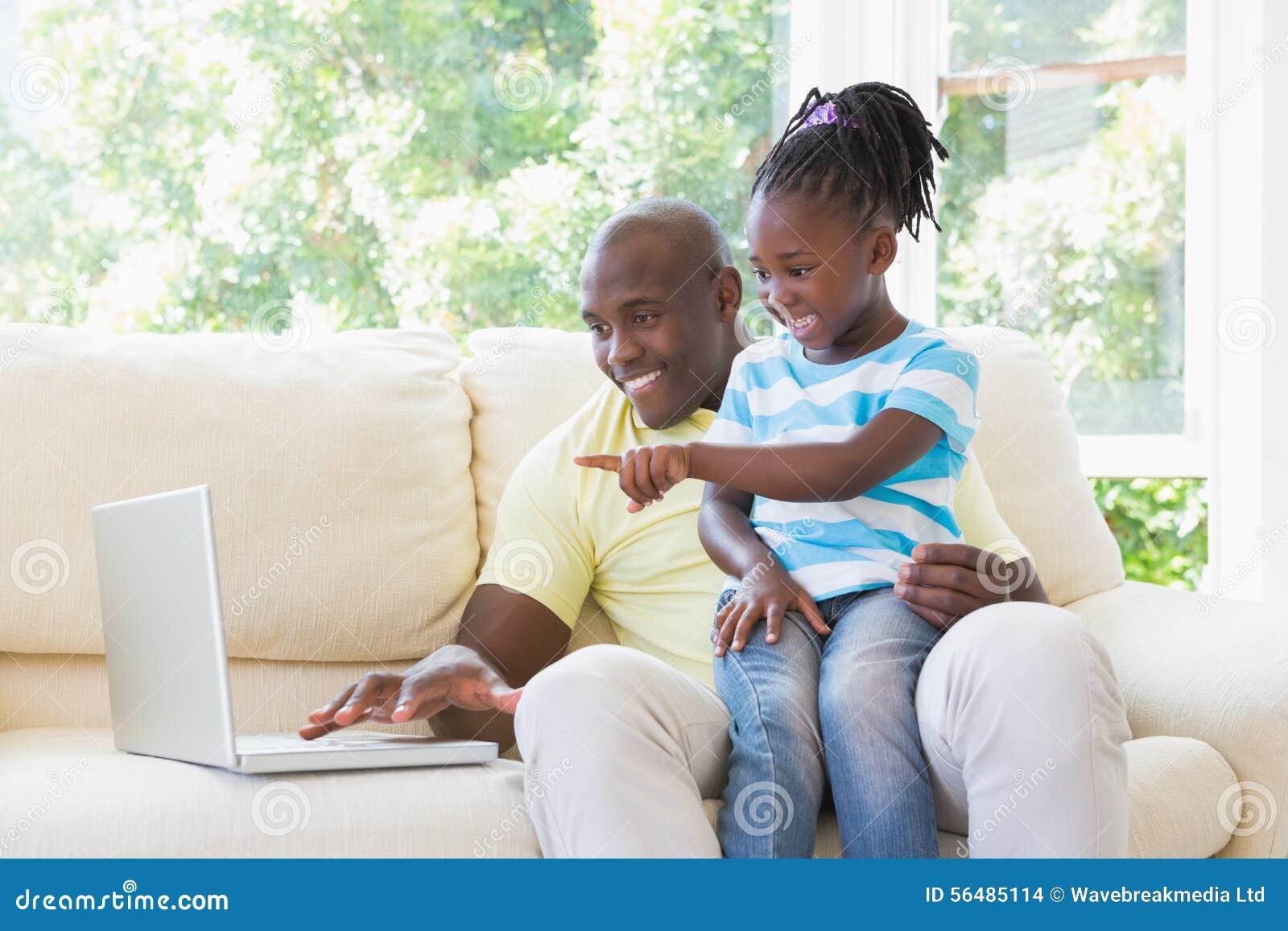 Père de sourire heureux à l aide de l ordinateur portable avec sa fille sur le divan