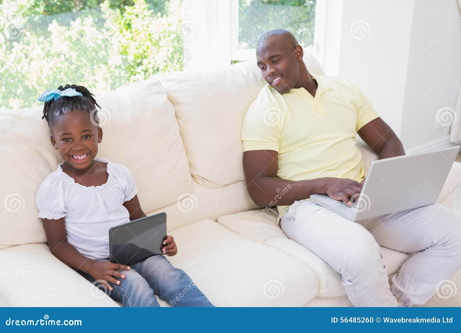 Père de sourire heureux à l aide de l ordinateur portable et sa fille à l aide du comprimé sur le divan