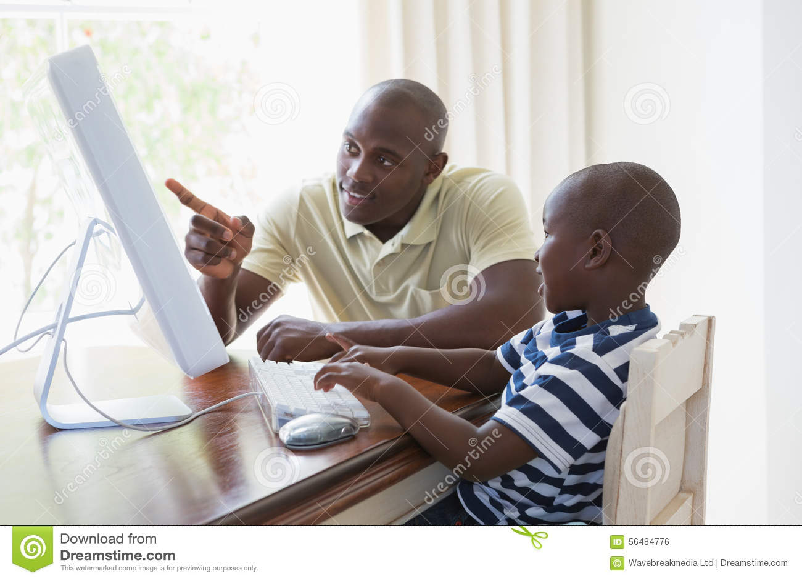 Père de sourire heureux avec son fils à l aide de l ordinateur