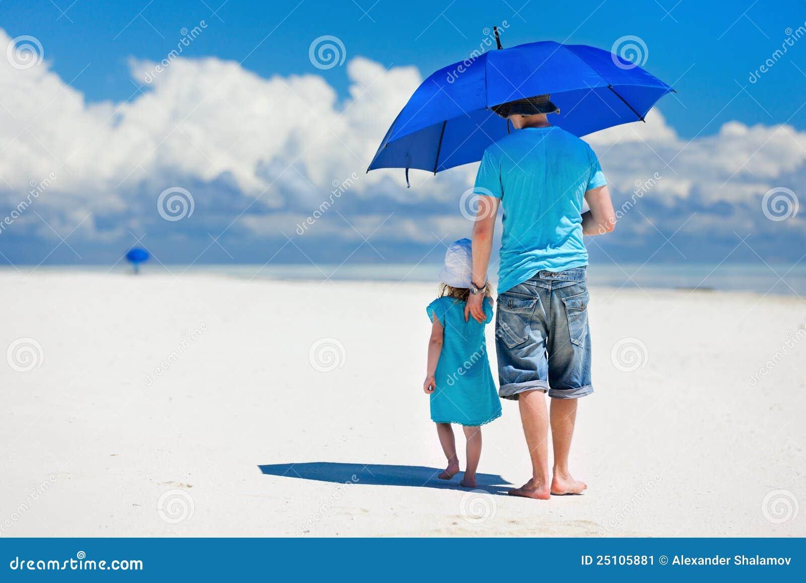 Père et descendant marchant à la plage