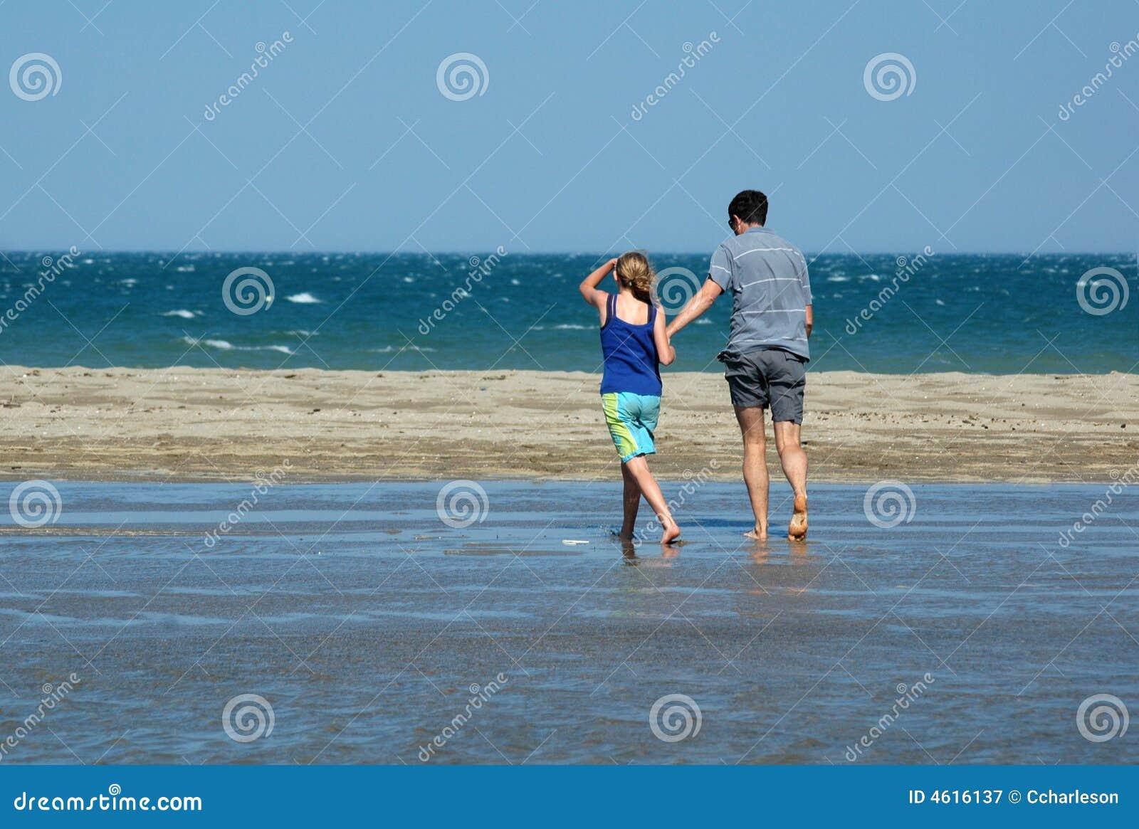 Père et descendant marchant sur la plage