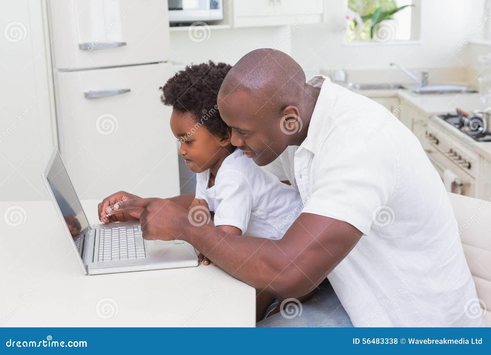 Père et fils à l aide de l ordinateur portable sur le divan