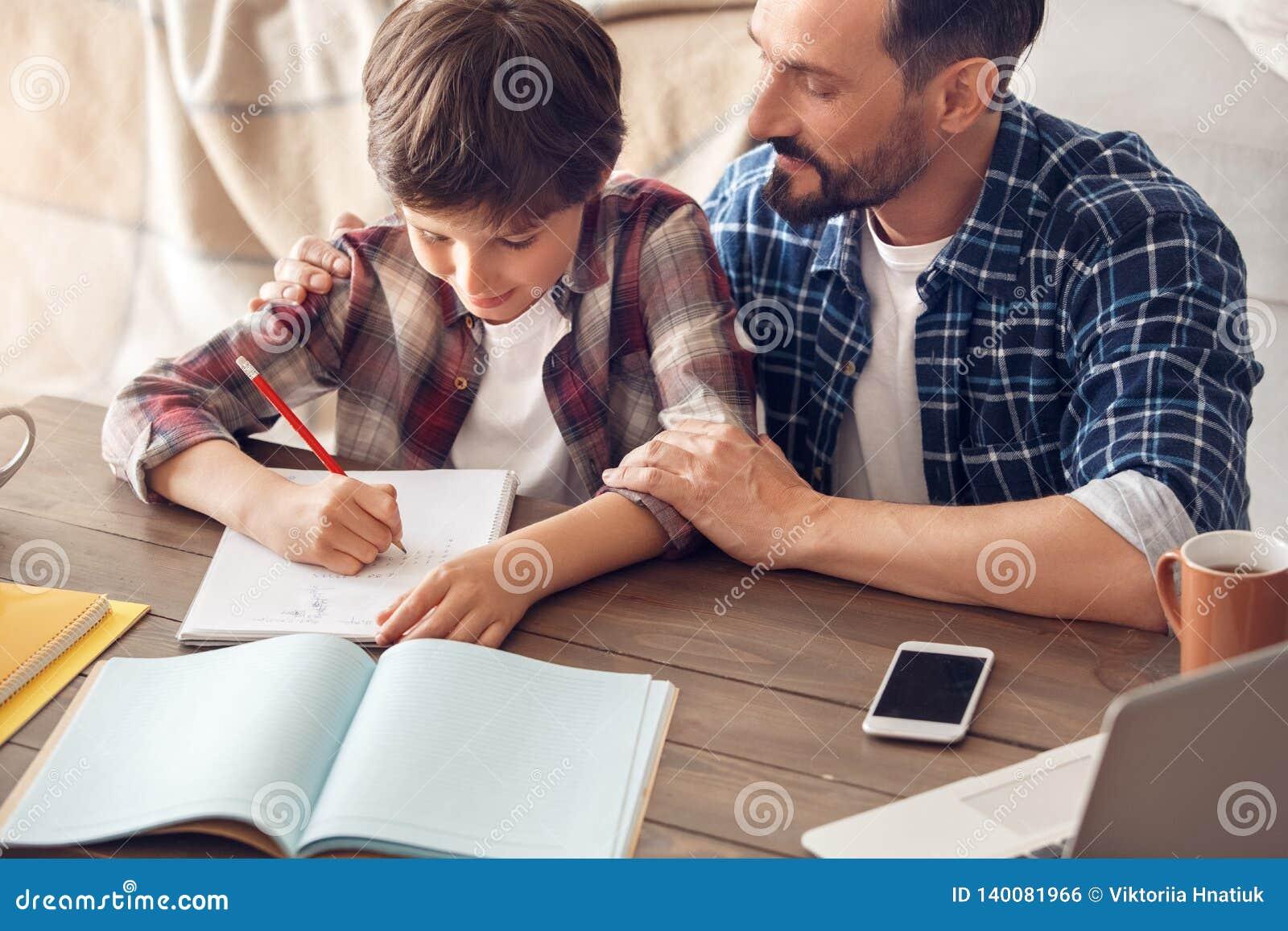 Père et fils à la maison s asseyant au papa de table étreignant le garçon écrivant le plan rapproché heureux de sourire de travai