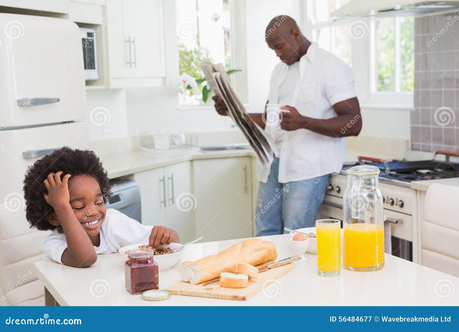 Père et fils de sourire prenant un petit déjeuner